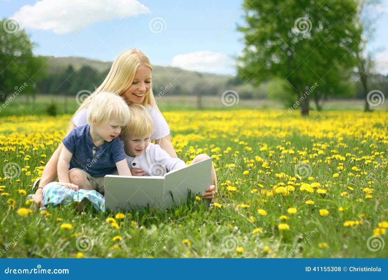 Livre d histoire de lecture de mère à deux enfants en bas âge dehors dans Meado