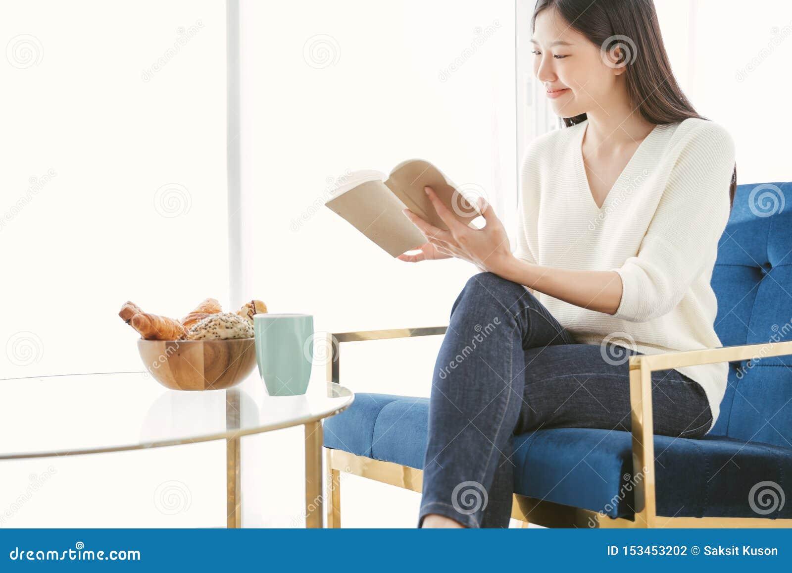 Livre de lecture asiatique de femme de portrait et détente avec du café à la maison