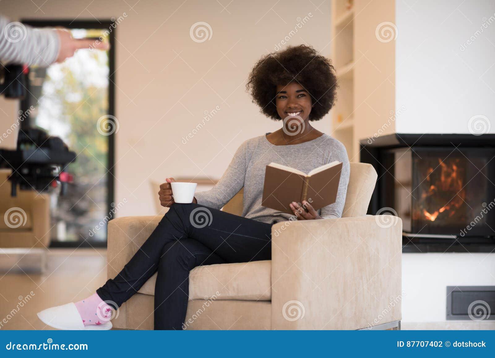 Livre de lecture de femme de couleur devant la cheminée