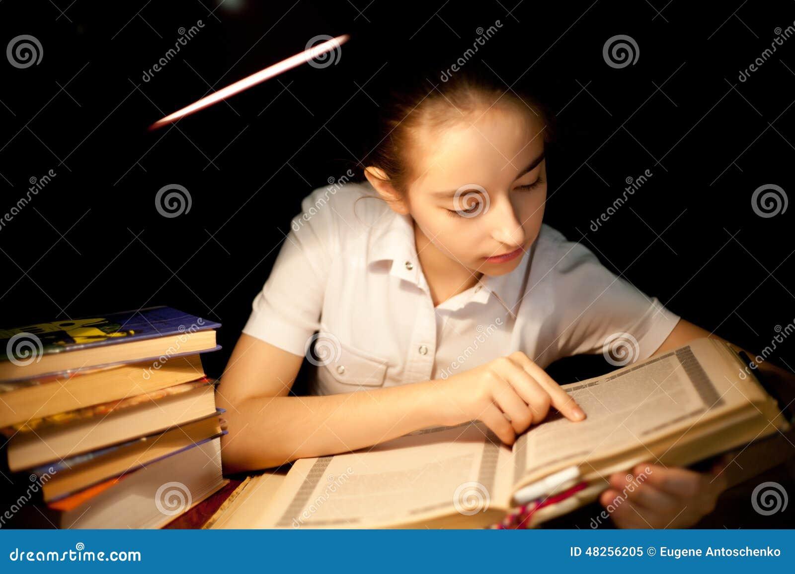 Livre de lecture de jeune fille à l obscurité de nuit à la bibliothèque