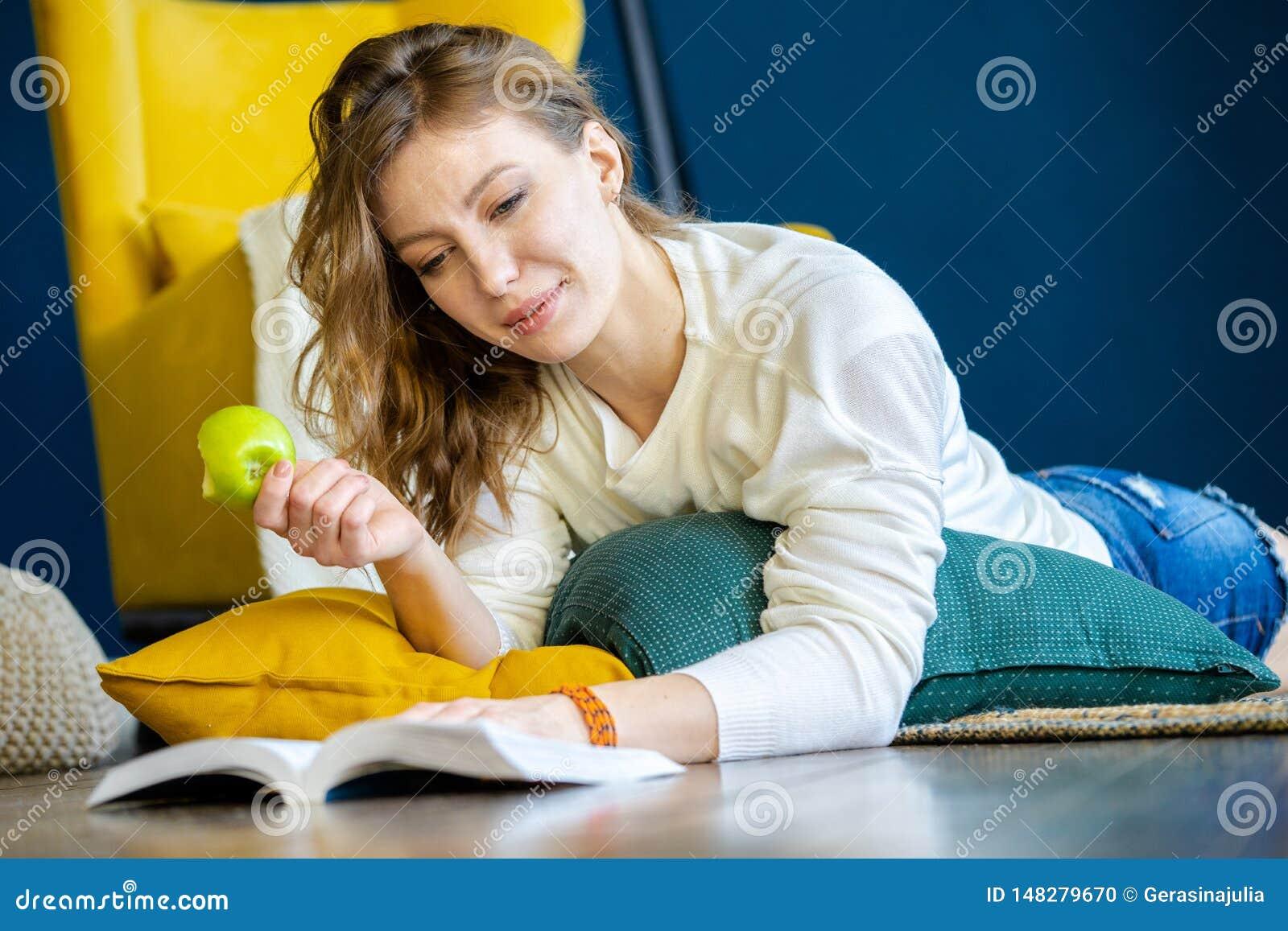 Livre de lecture de femme à la maison et s étendant sur le plancher à côté du fauteuil jaune