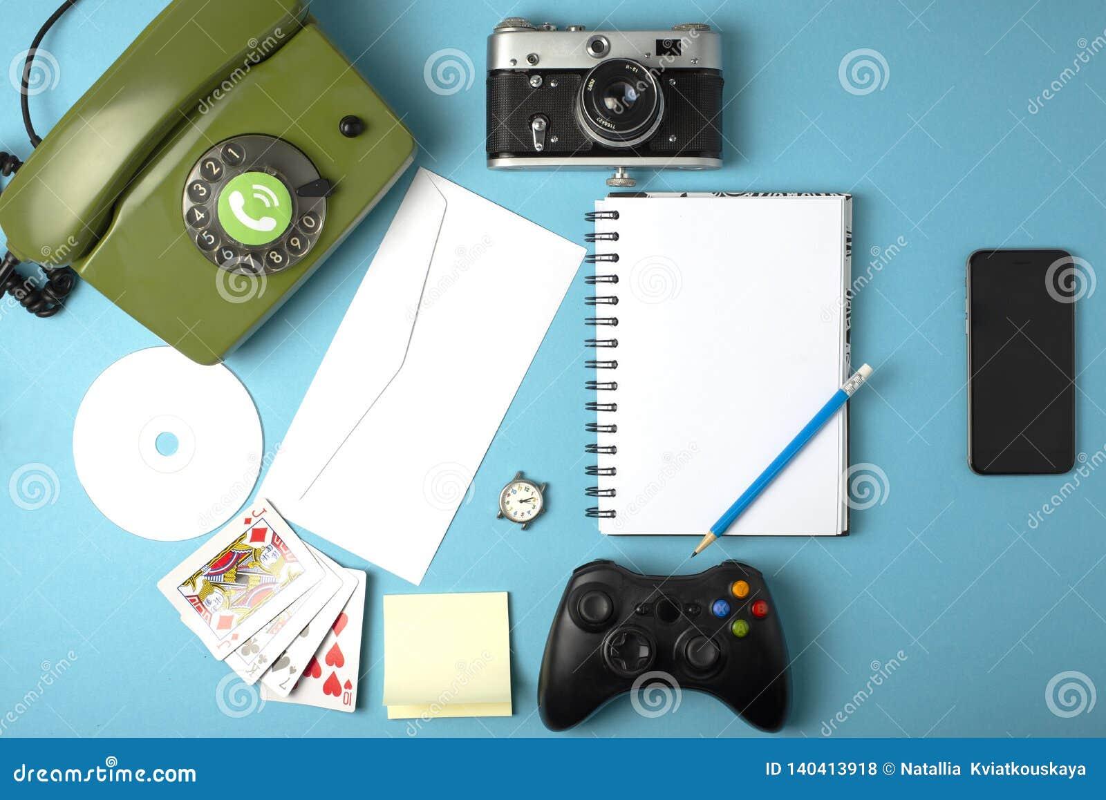 Livre, horloge, caméra, téléphone, jeu, carnet, CD, crayon combiné dans un téléphone portable Concept sur un fond de couleur