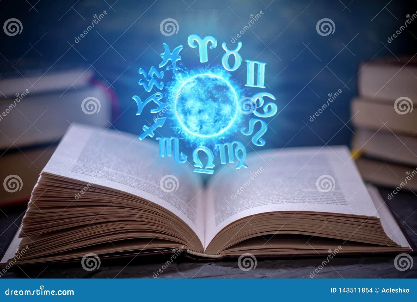 Livre ouvert sur l astrologie sur un fond foncé Le globe magique rougeoyant avec des signes du zodiaque dans la lumière bleue