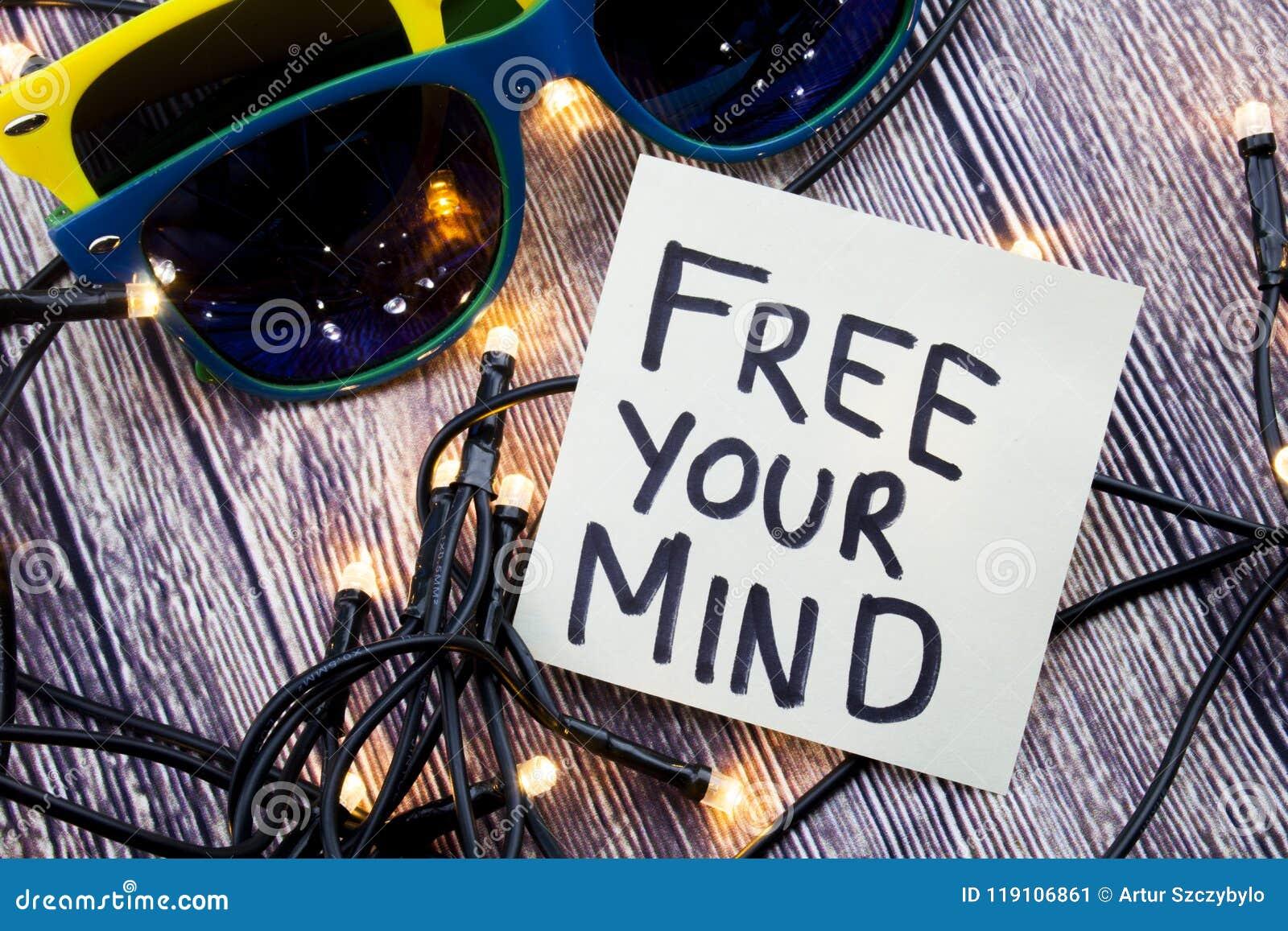 Livre sua mente um conceito do incentivo em um papel de nota Algumas luzes são mostradas na ordem discreta Dois óculos de sol da