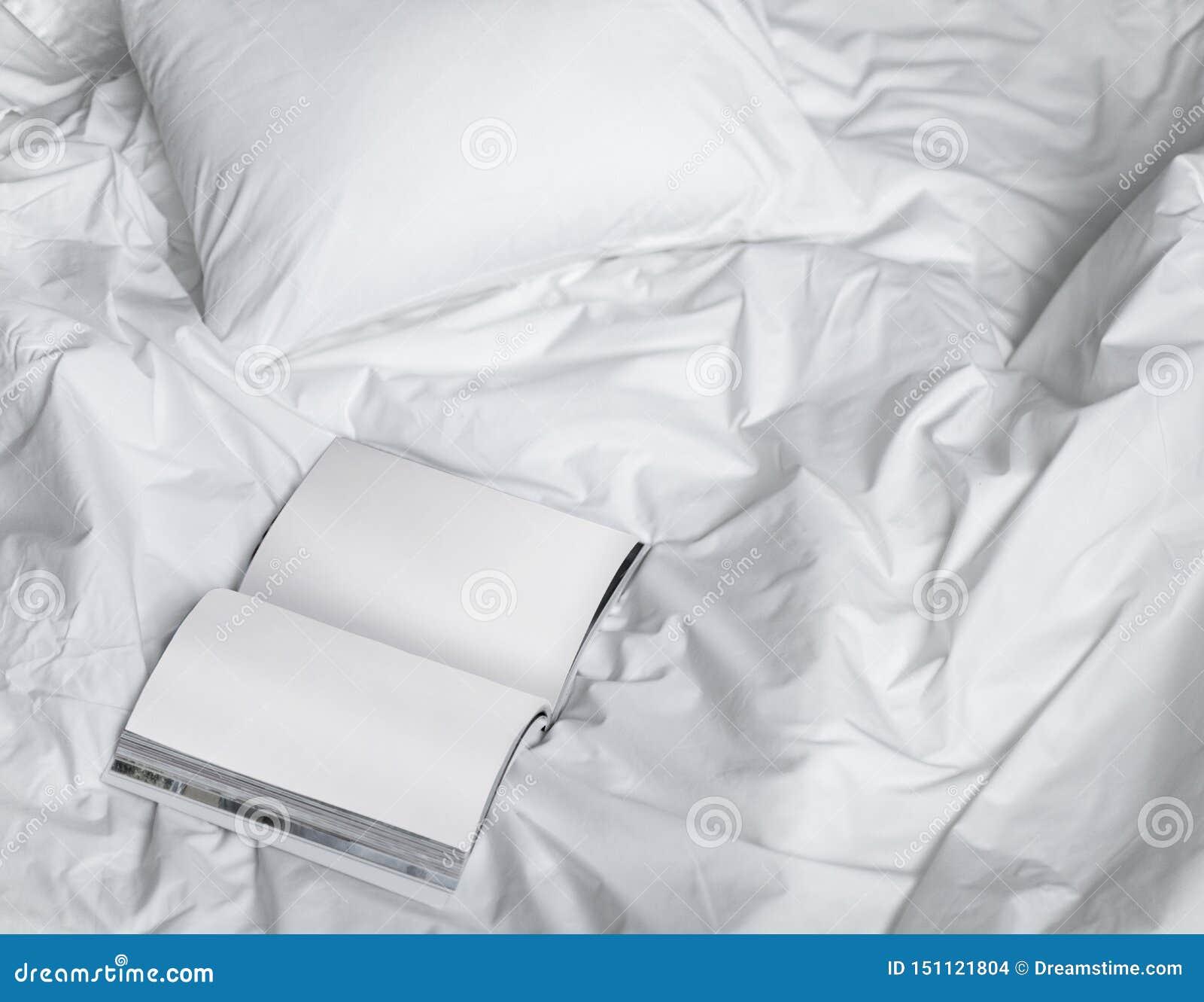 Livre sur le lit malpropre, composition créative en photo avec le livre et lit blanc sous la lumière du soleil de la fenêtre