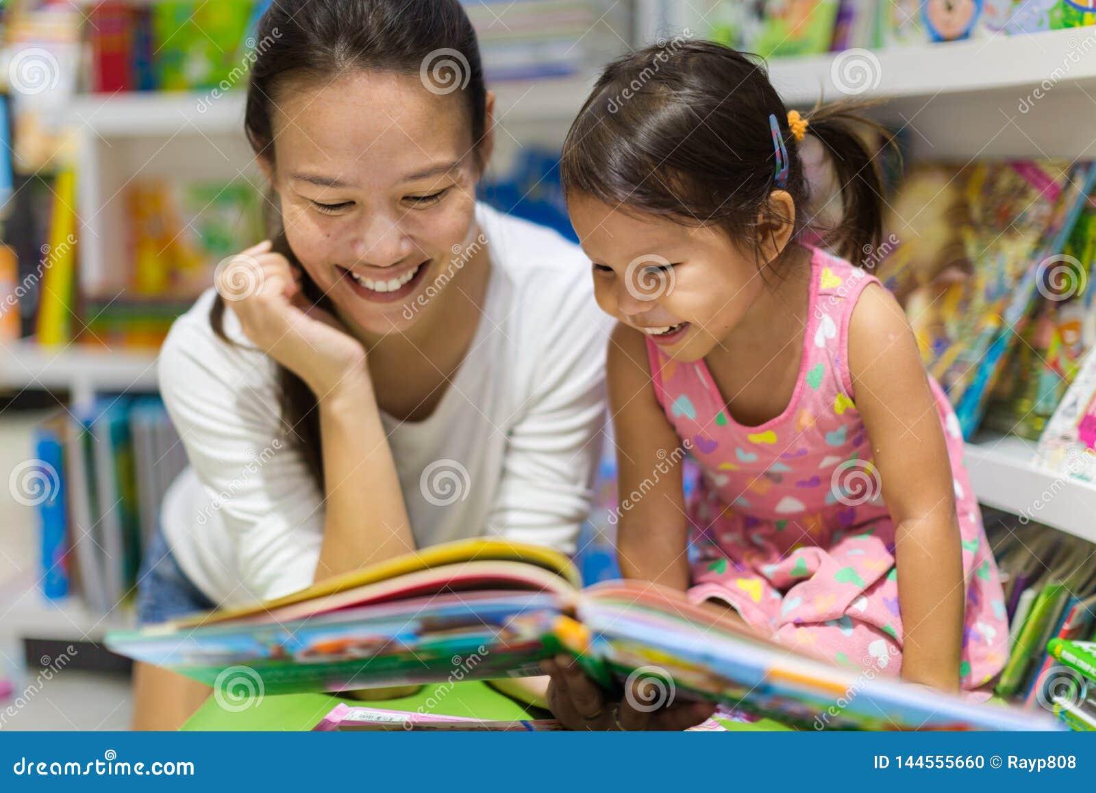 Livres de lecture de parent et d enfant ensemble dans la bibliothèque
