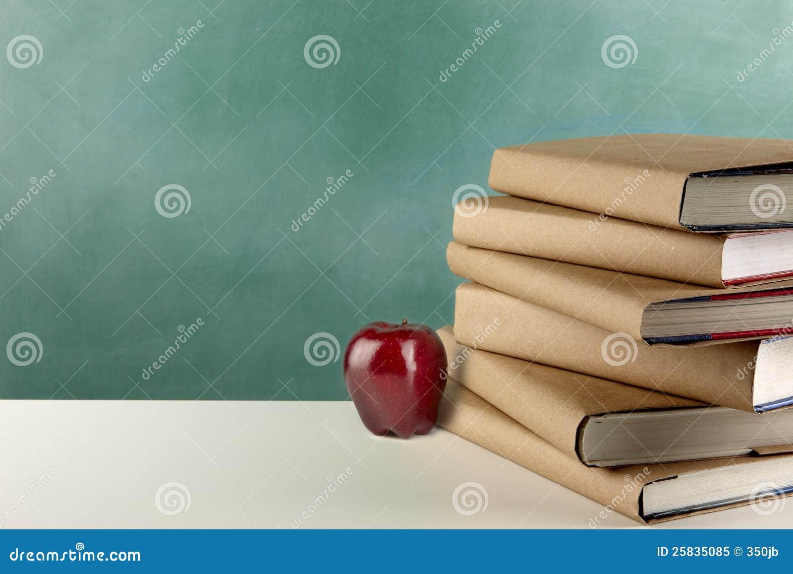 Livres, pomme et tableau noir d école