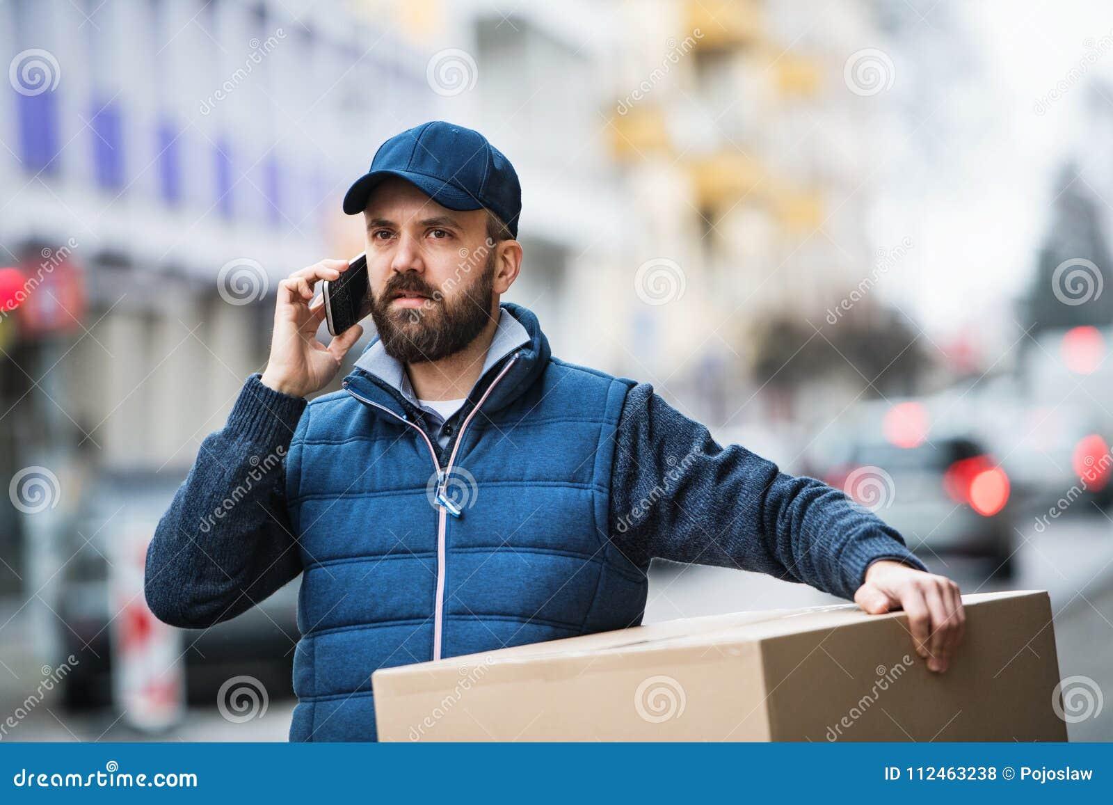 Livreur avec une boîte de colis sur la rue