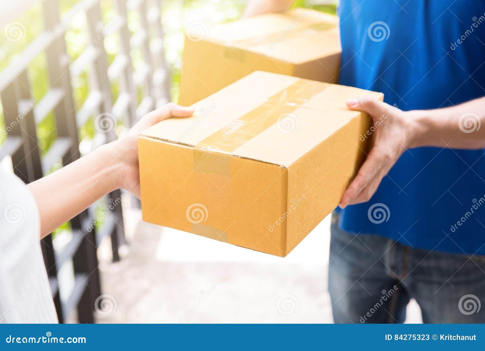 Livreur dans la boîte de remise uniforme bleue de colis au destinataire