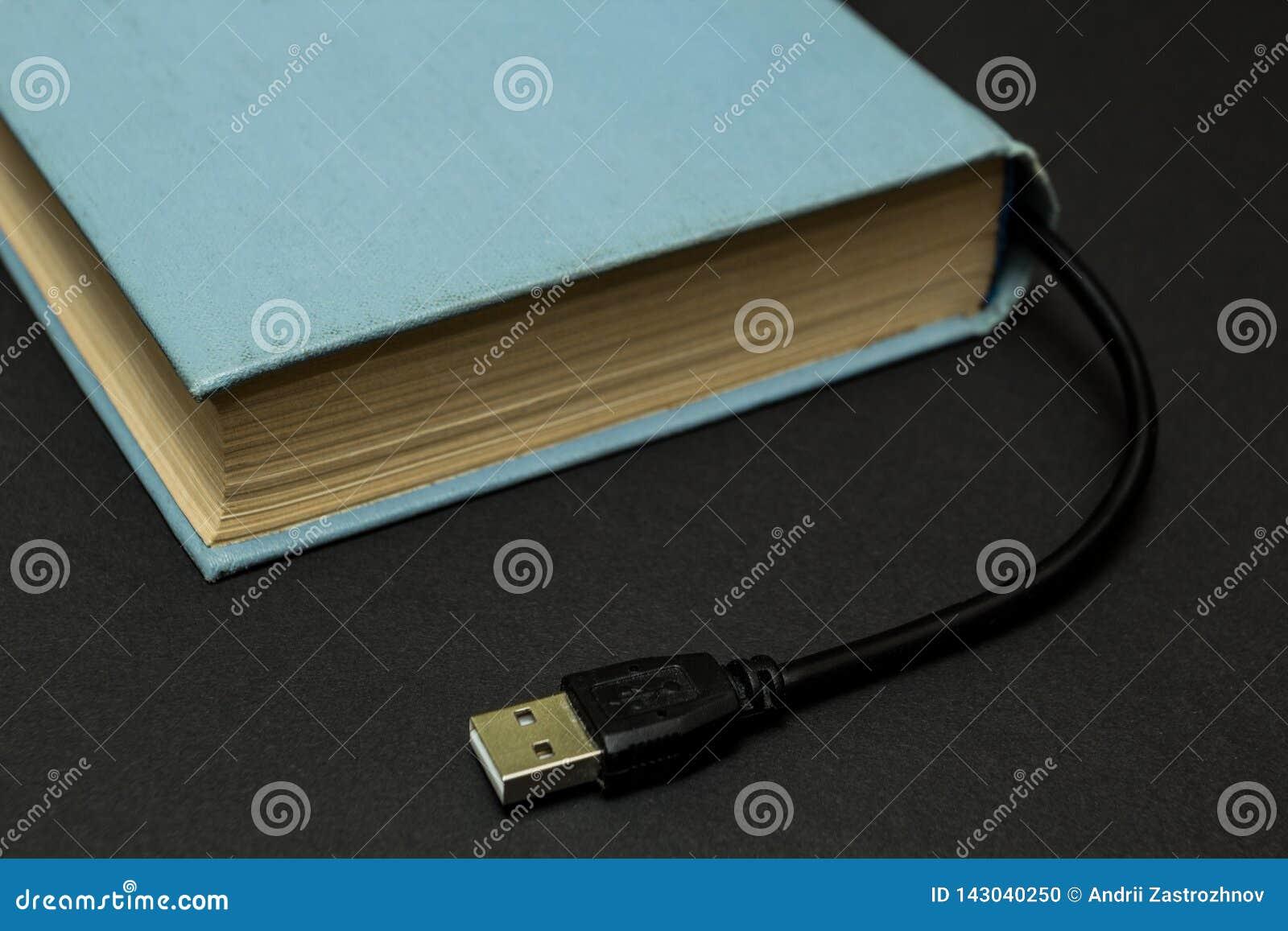 Livro azul com um conector de USB em um fundo preto