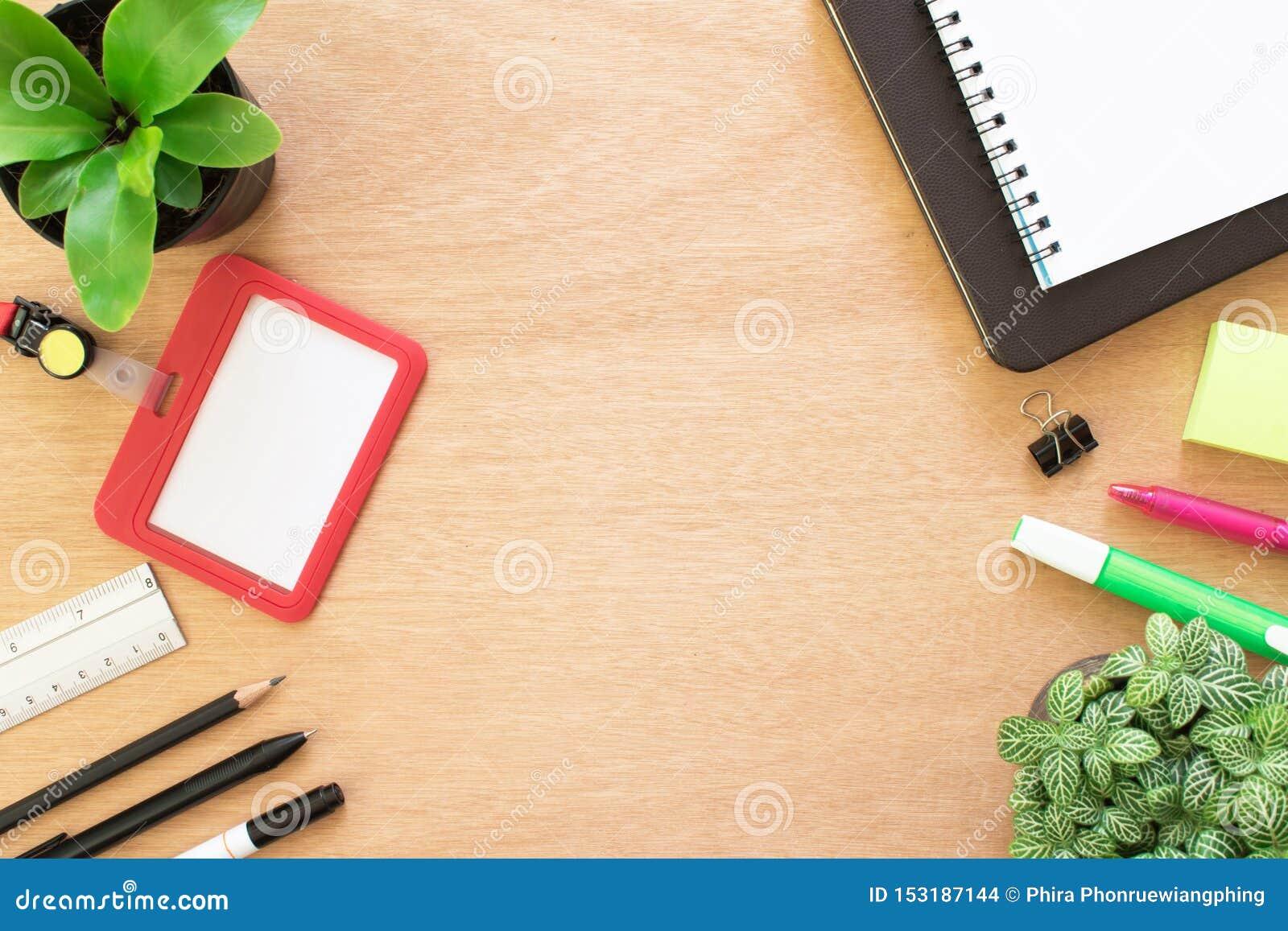 Livro, clipe, lápis, régua, destacando a pena, o cartão do empregado, o post-it e o potenciômetro da árvore na mesa de madeira ma