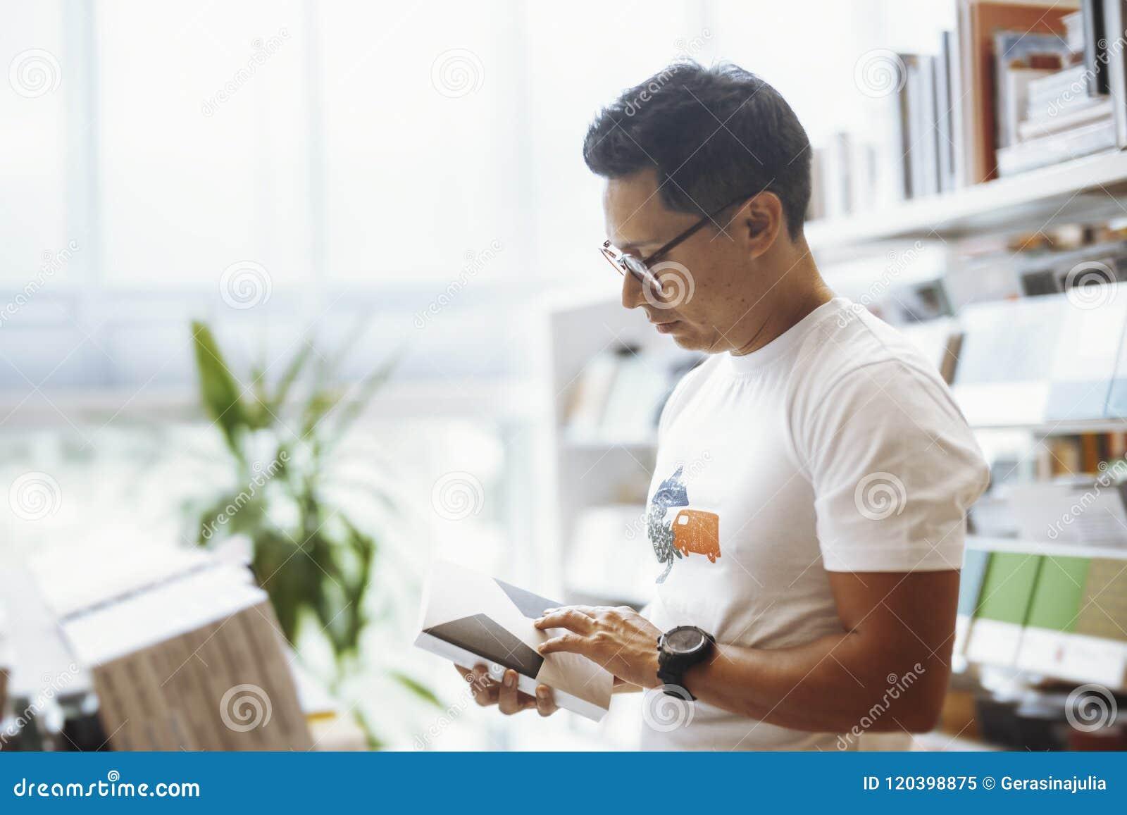 Livro de leitura de óculos novo do homem em livrarias modernas brilhantes