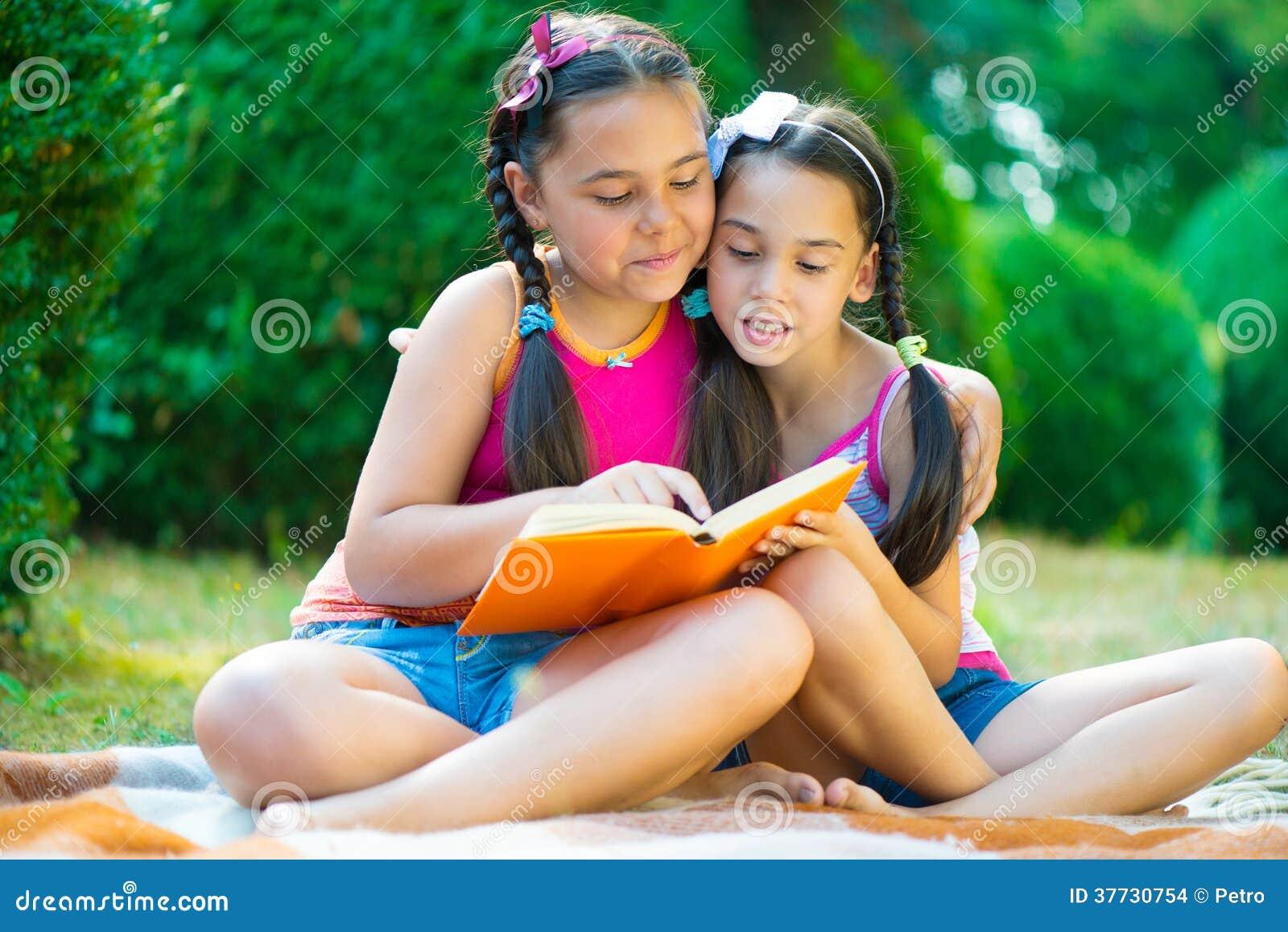 Livro de leitura das irmãs no parque do verão