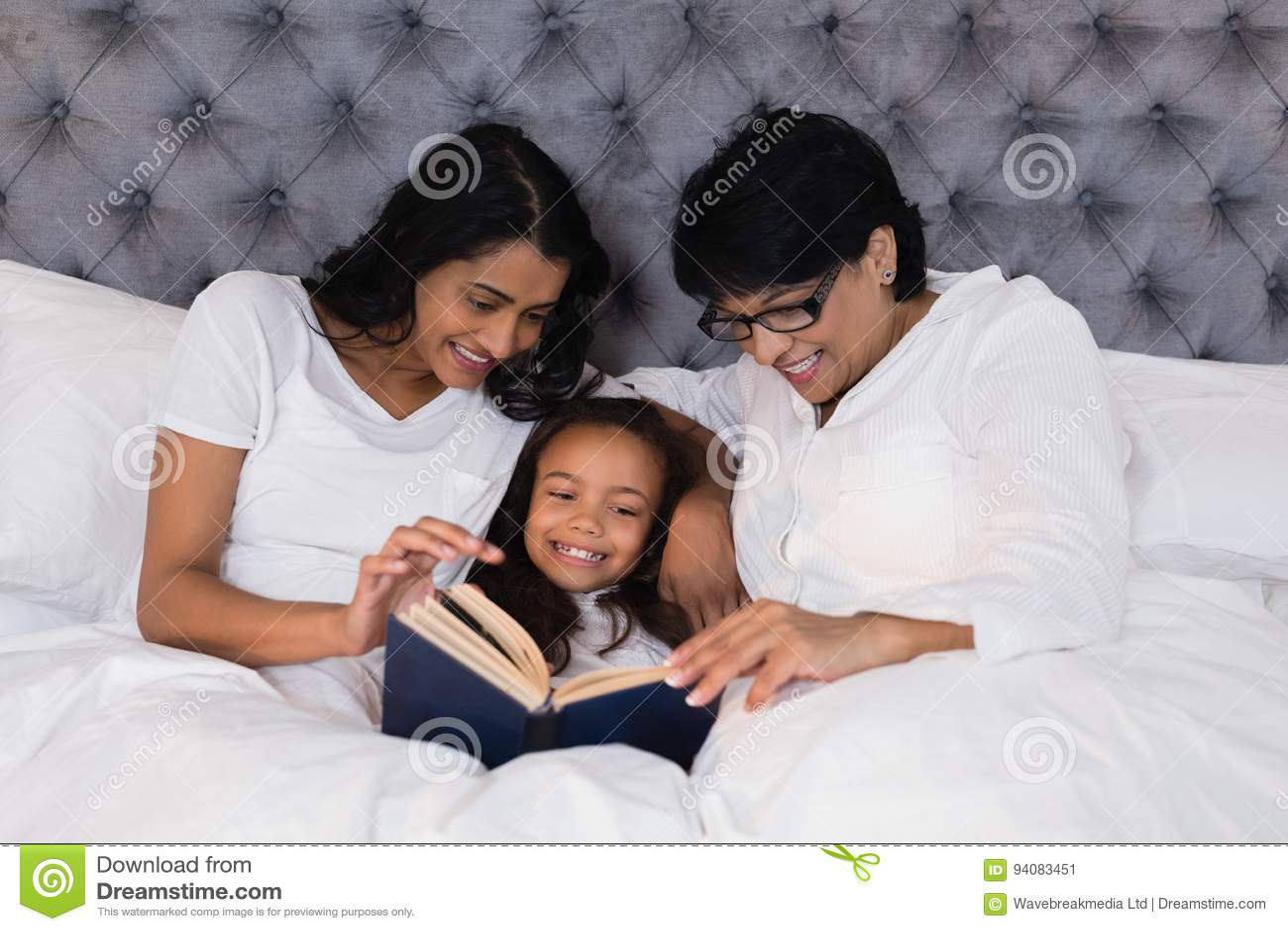 Livro de leitura de sorriso da família da multi-geração ao descansar na cama