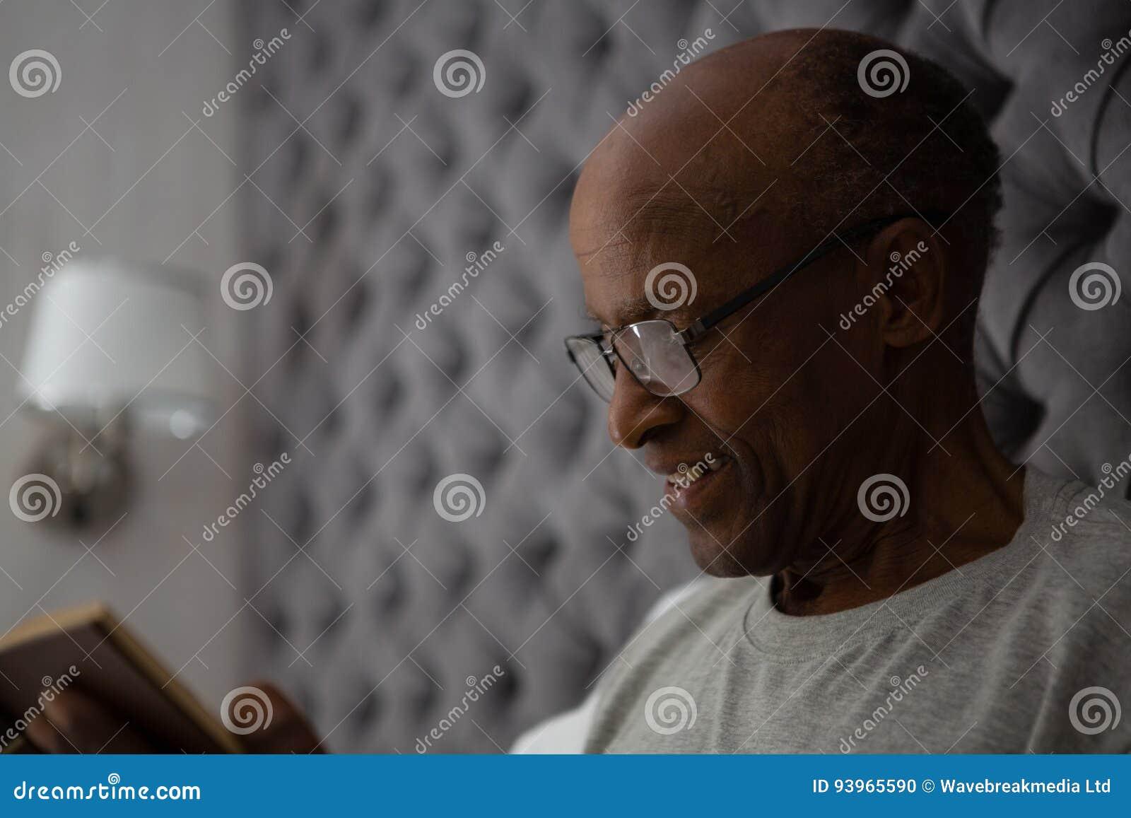 Livro de leitura de sorriso do homem superior ao descansar na cama