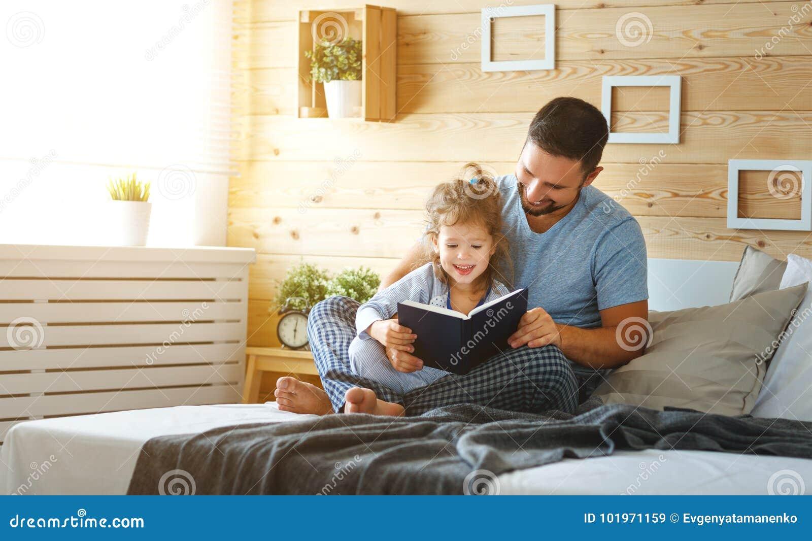 Livro de leitura feliz do pai e da filha da família na cama