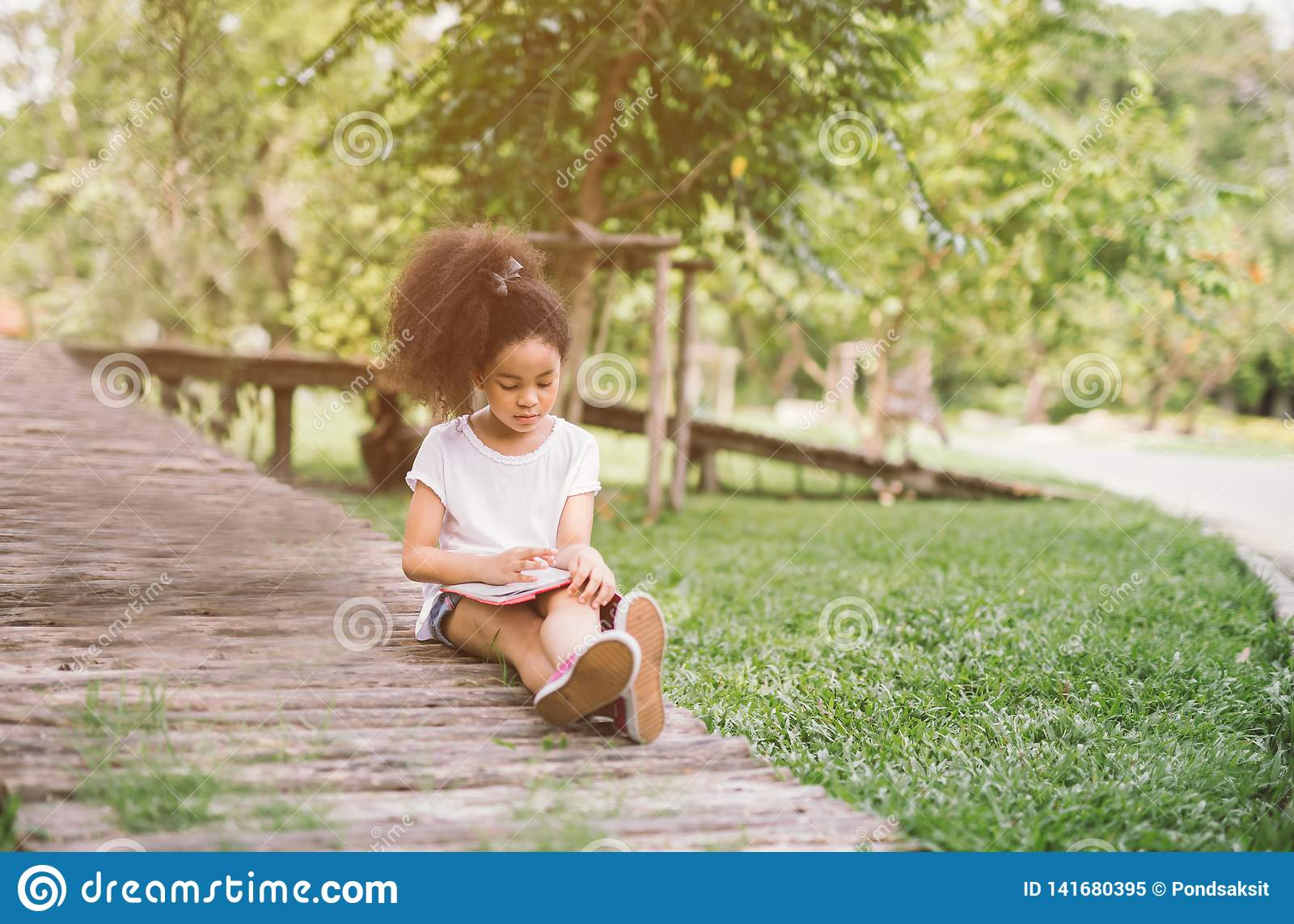 Livro de leitura pequeno da menina da criança do Afro entre o jardim verde do prado dos pontos