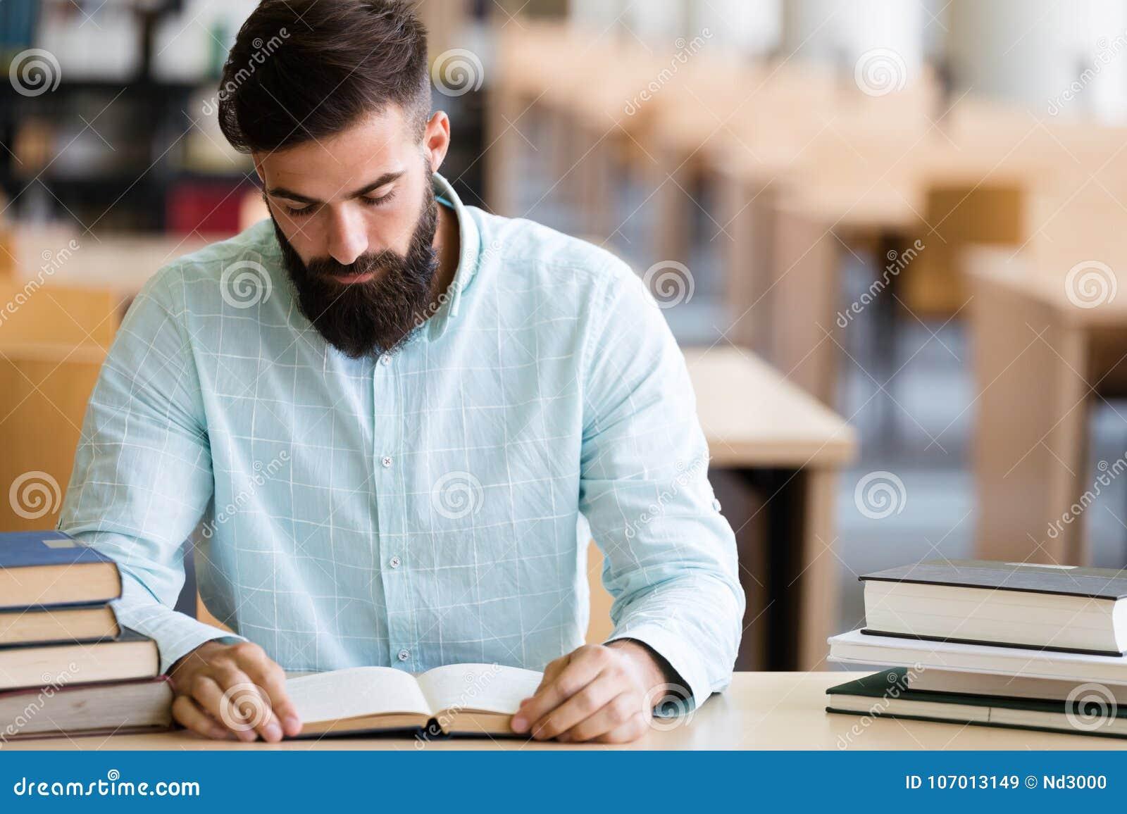 Livro de leitura sério do estudante masculino na biblioteca de faculdade