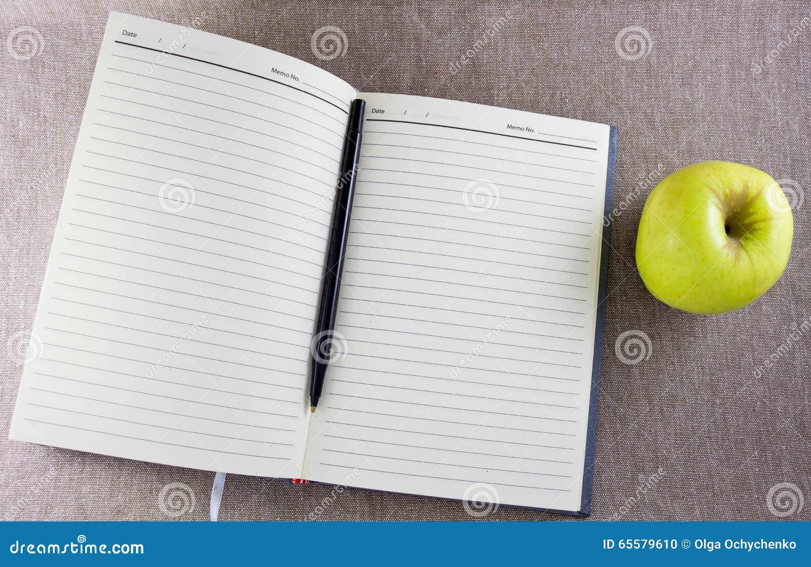 Livro de observação aberto com maçã verde
