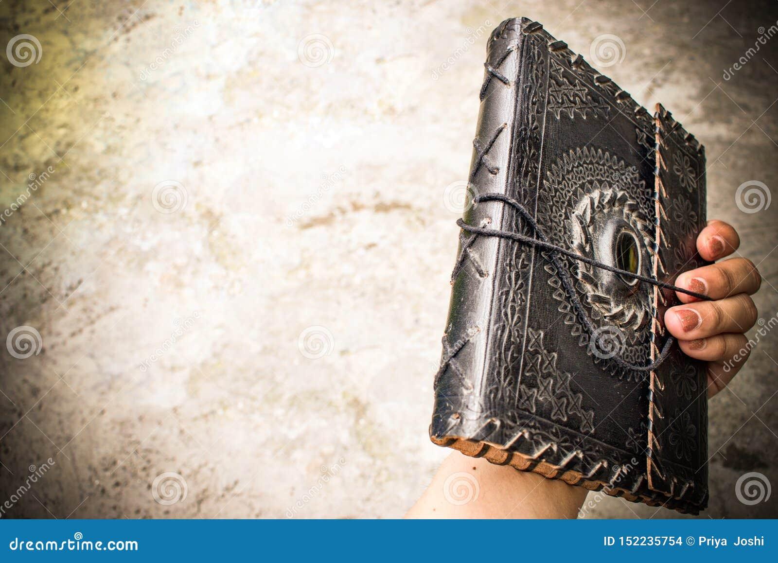 Livro encadernado de couro velho antigo no ósmio da mão uma mulher