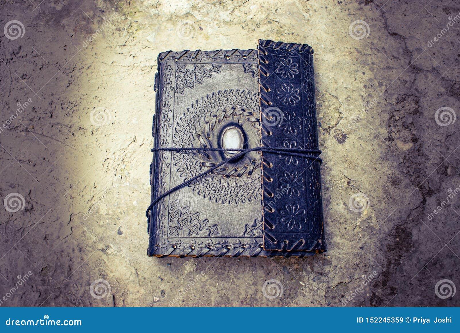 Livro encadernado de couro velho antigo que encontra-se na terra
