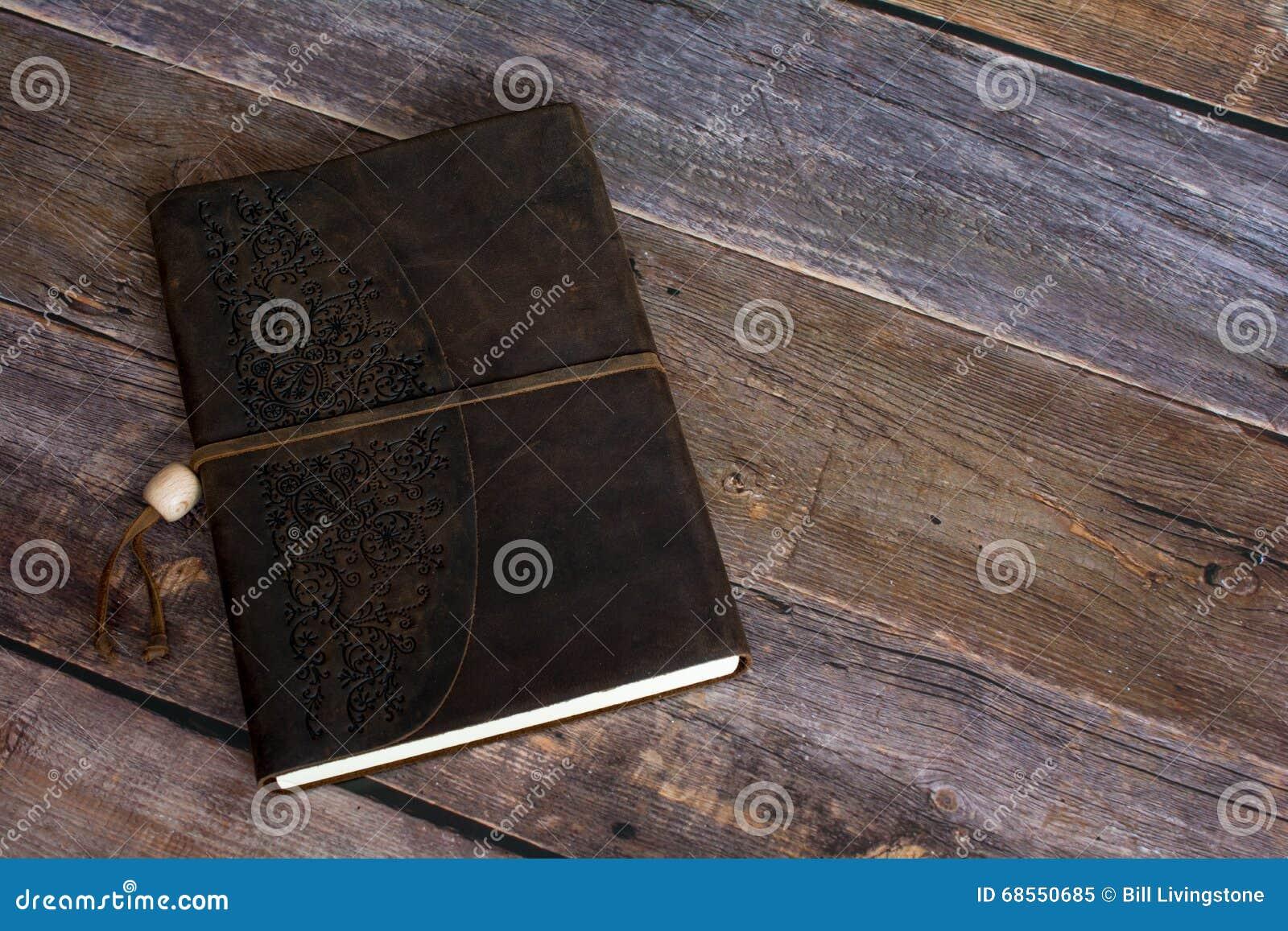 Livro encadernado do jornal do couro clássico em um fim velho do assoalho da placa do celeiro acima