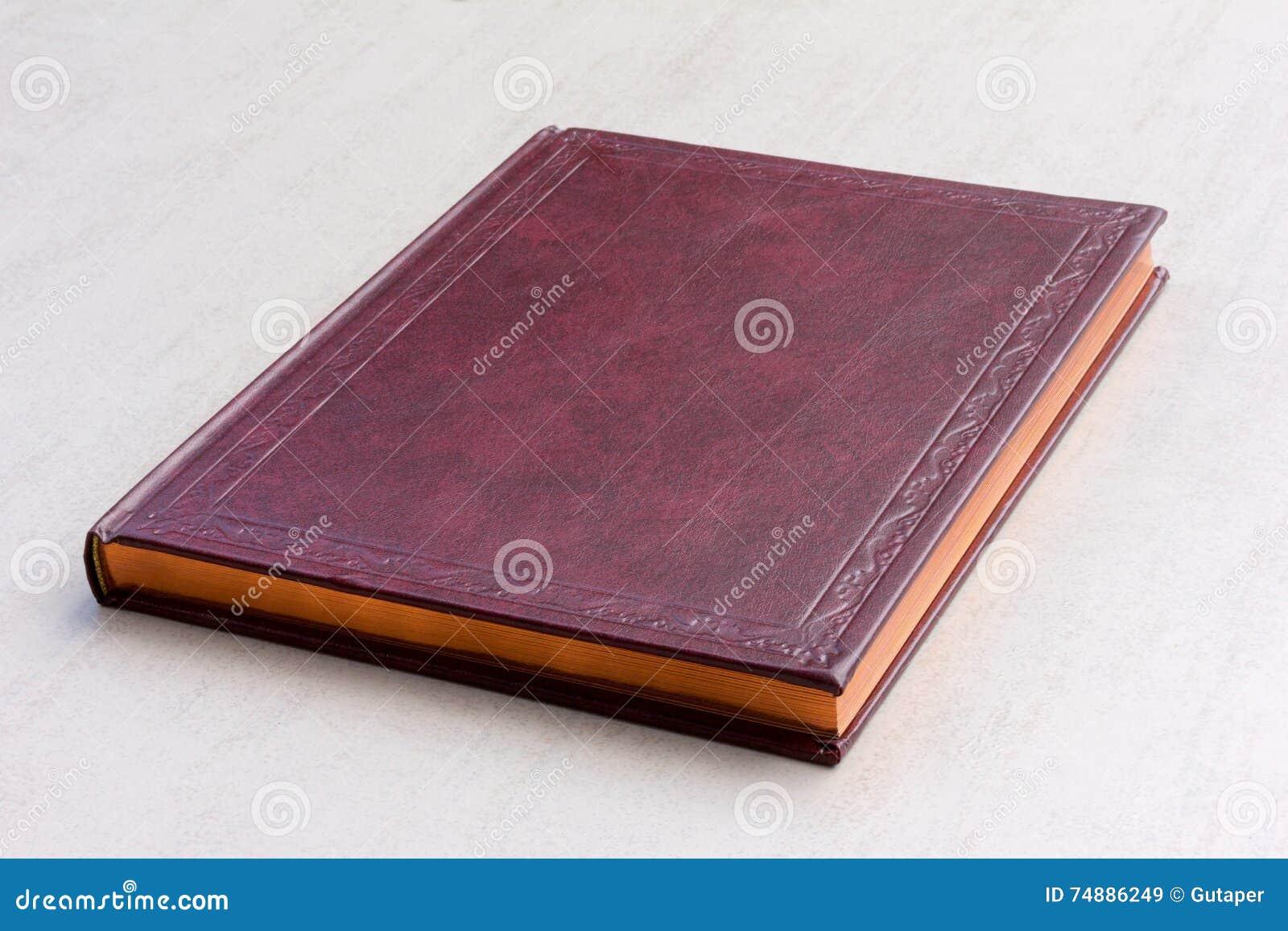 Livro roxo com as páginas do ouro no fundo cinzento