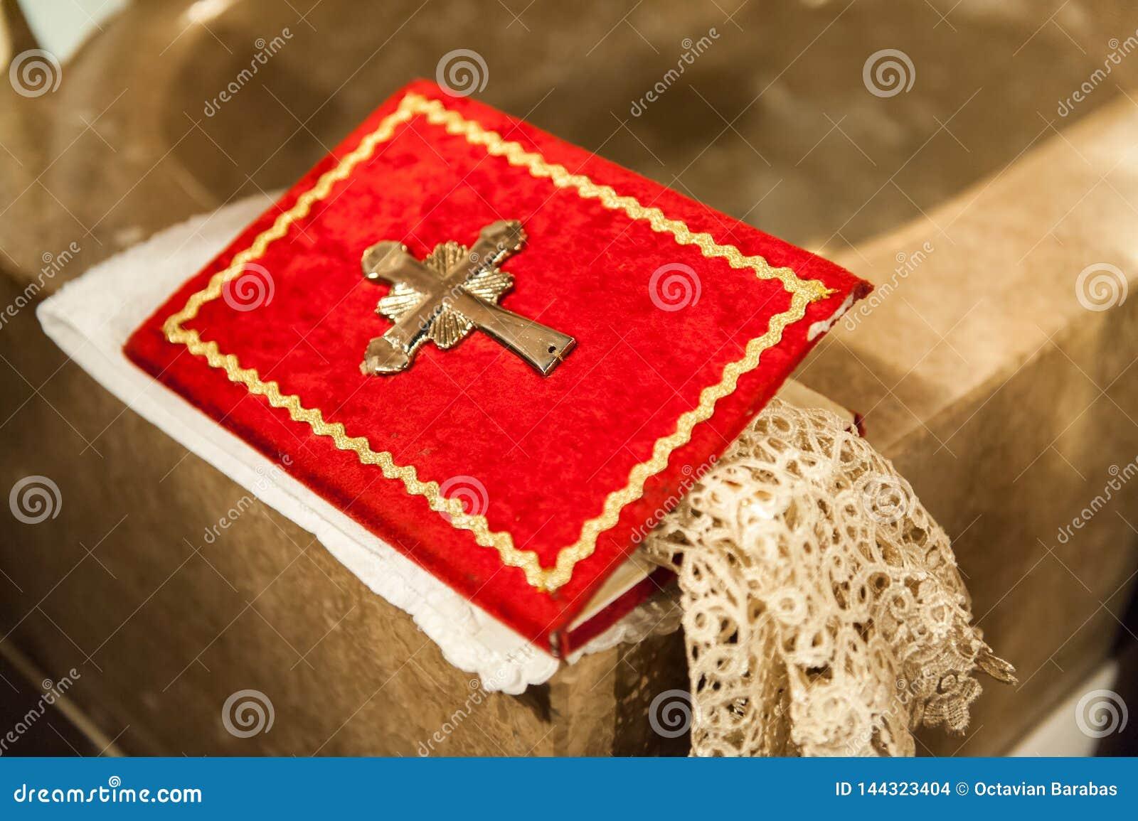 Livro vermelho do azevinho com cruz do metal na igreja