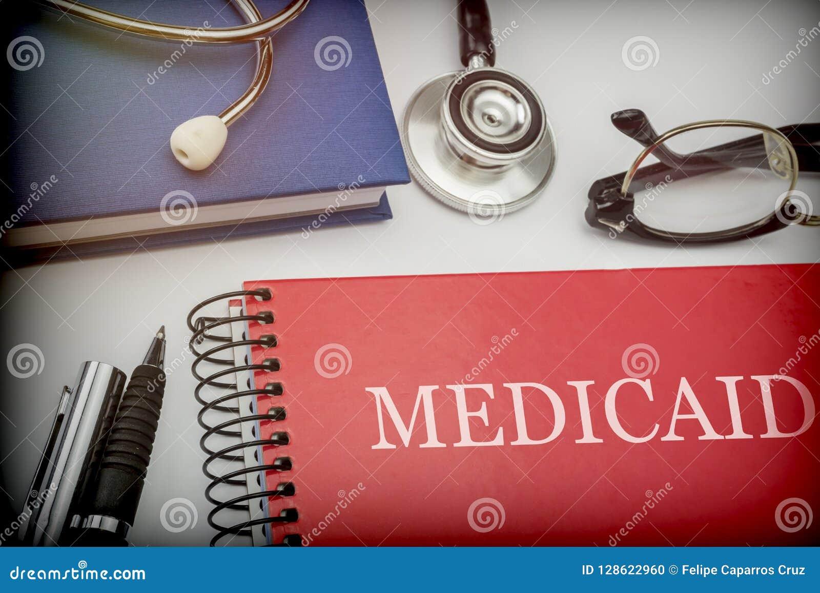 Livro vermelho intitulado medicaid junto com o equipamento médico
