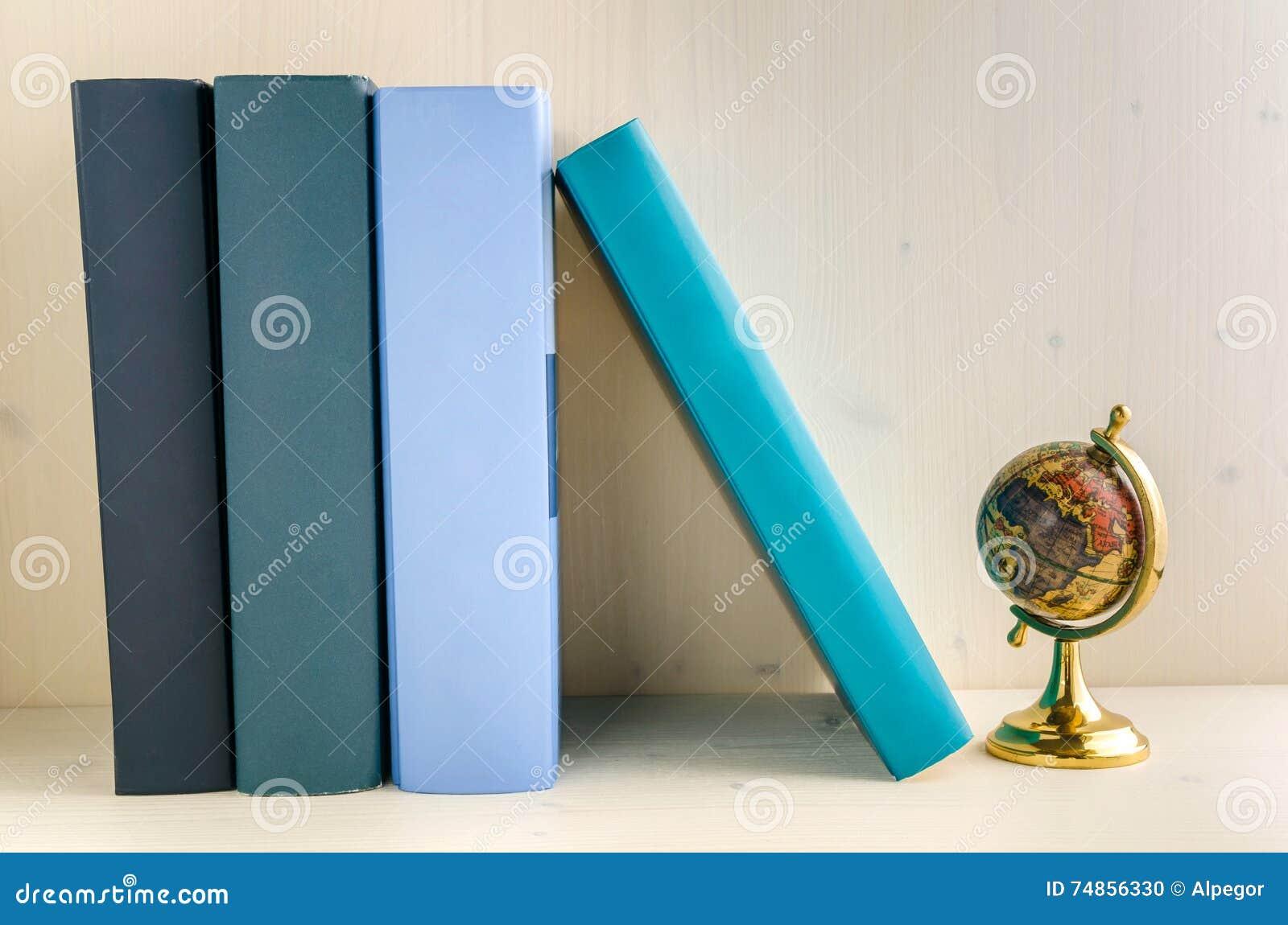 Livros do livro encadernado e um globo em uma prateleira