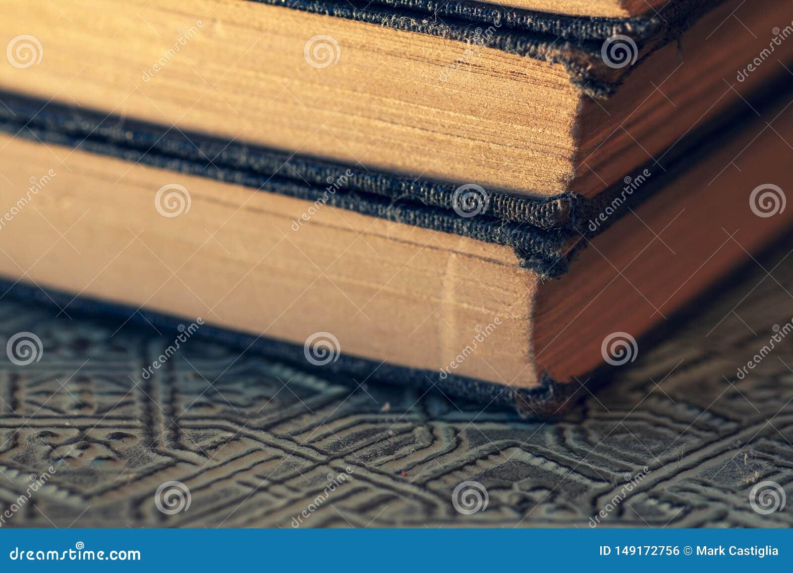Livros gastos velhos empilhados em fim de superf?cie textured acima