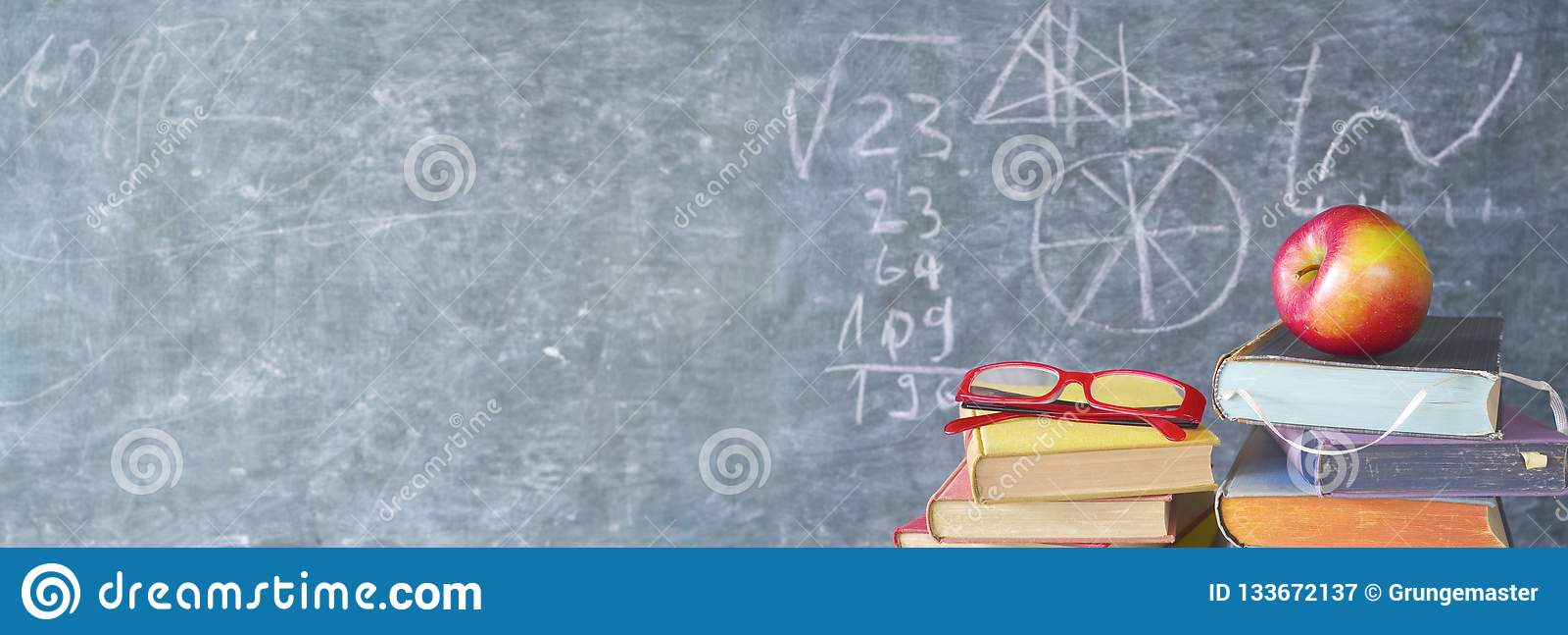 Livros, maçã, especs. na frente de uma placa preta, de volta à escola