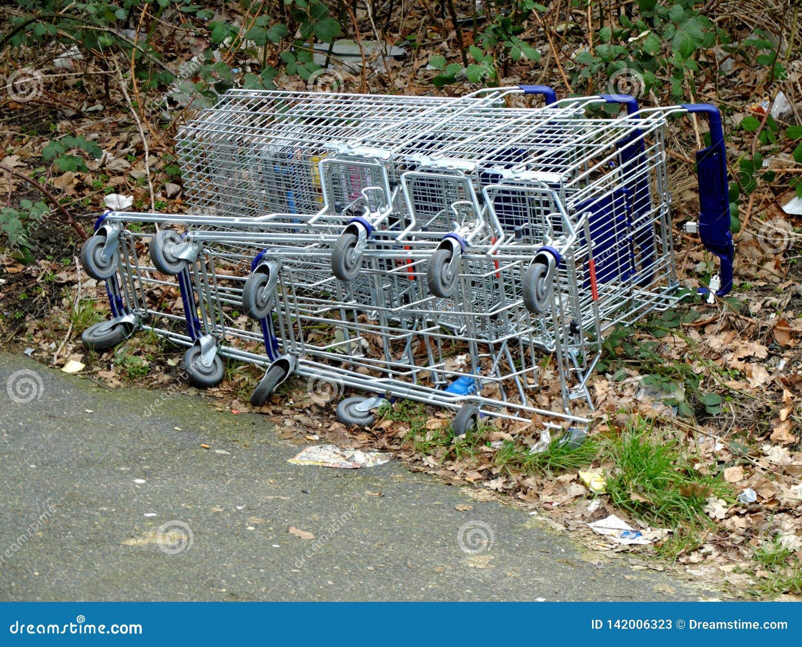 Livsmedelsbutikvagnar som är stupade och lägger på jordningen Begreppet av tomma supermarket, droppe i försäljningar, slut upp av