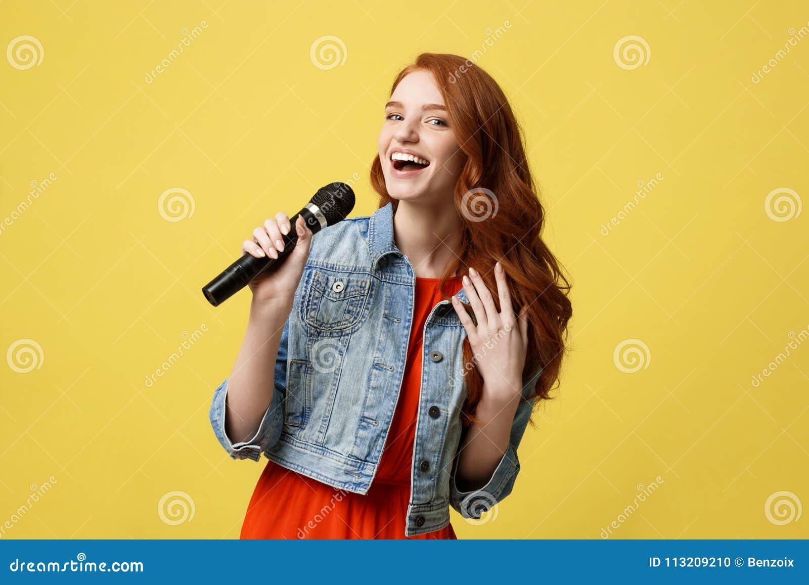 Livsstil och folkbegrepp: För hårmodell för uttrycksfull skönhet ljust rödbrun flicka i tillfällig jeantorkdukesångare med en mik