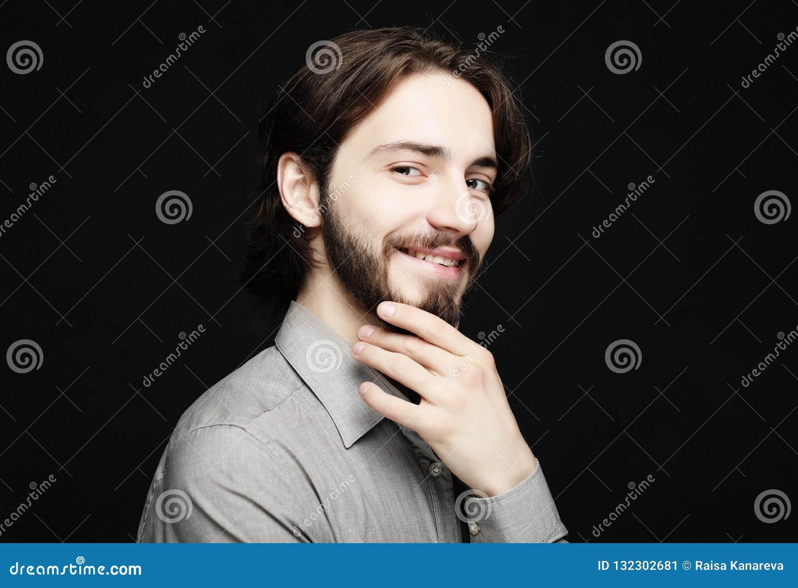Livsstil och folkbegrepp: Stående av den stiliga unga mannen med leende på mörk bakgrund