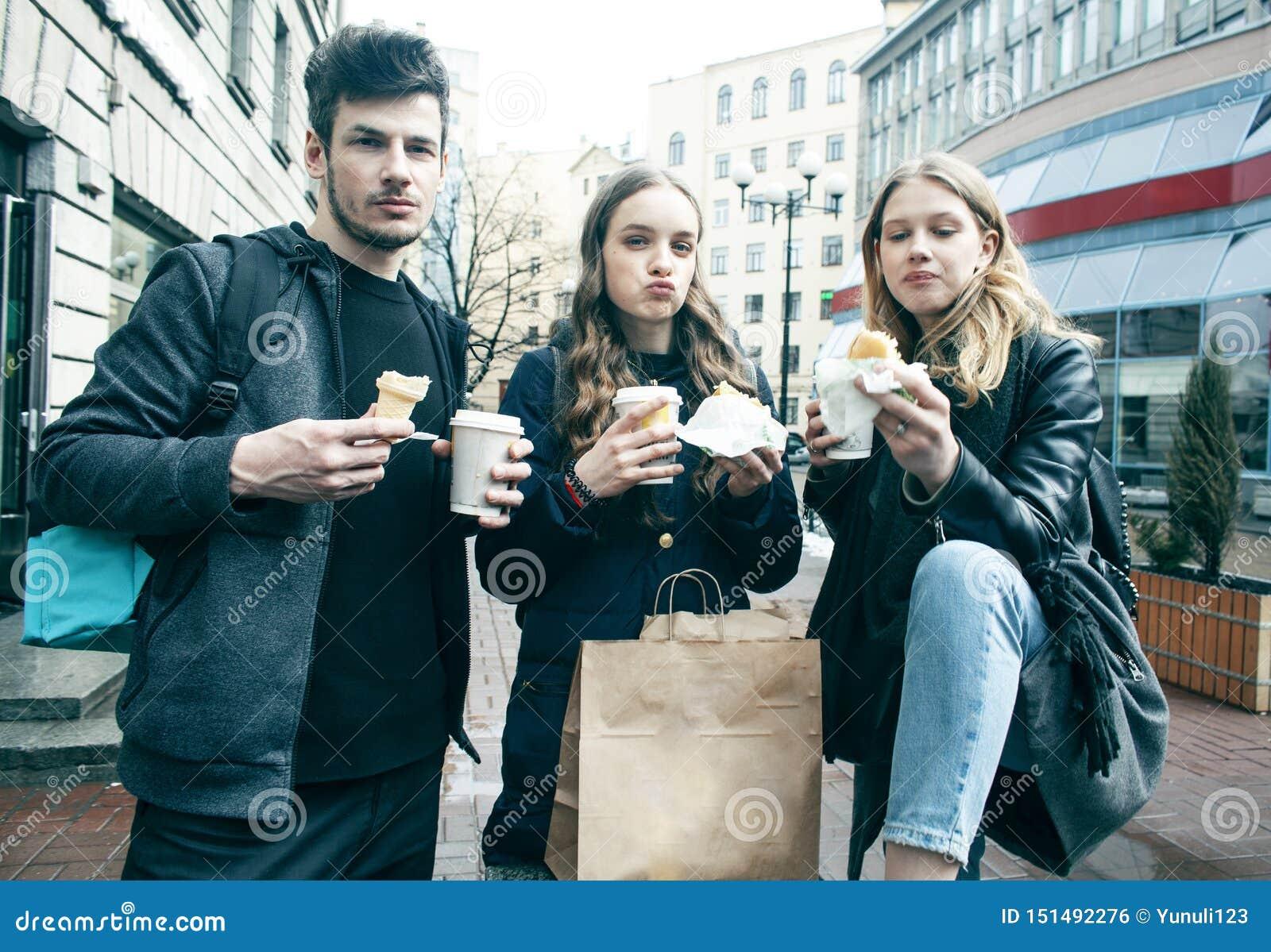 Livsstil och folkbegrepp: tv? flickor och grabb som ?ter snabbmat p? stadsgatan som har tillsammans gyckel som dricker kaffe