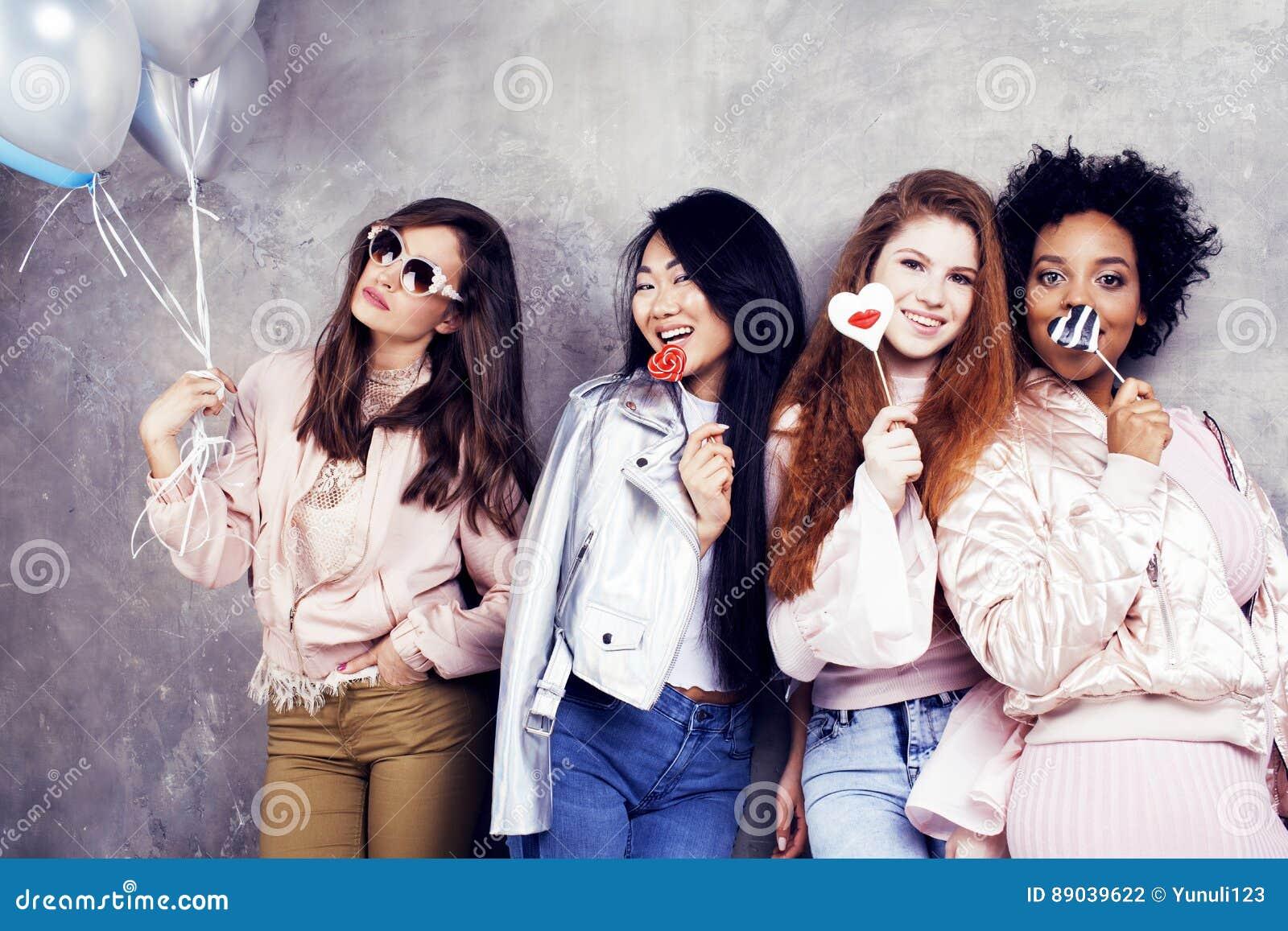 Livsstil och folkbegrepp: ung nätt mångfaldnationkvinna med olika ålderbarn som firar på födelsedag