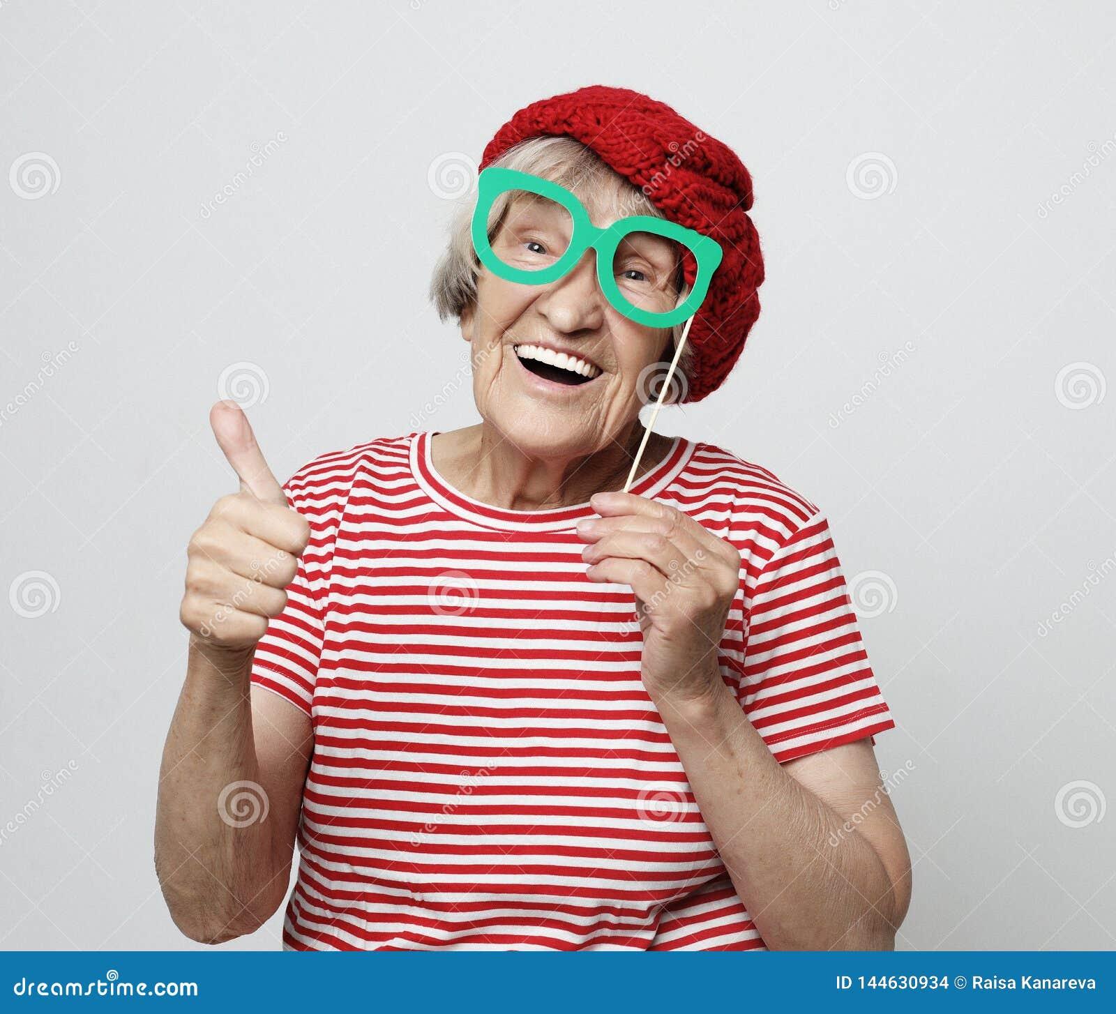Livsstil, sinnesr?relse och folkbegrepp: den roliga farmodern med fejkar exponeringsglas, skratt och ordnar till f?r parti
