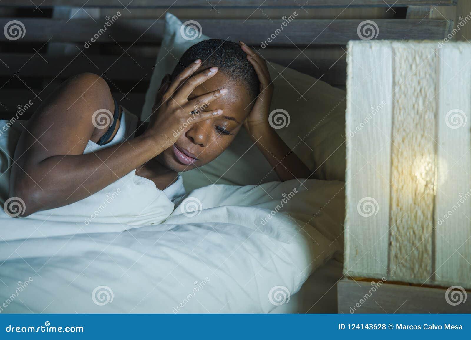 Livsstilnattstående av den unga ledsna och stressade svarta afrikansk amerikankvinnan som ligger på sängrubbningen som försöker a