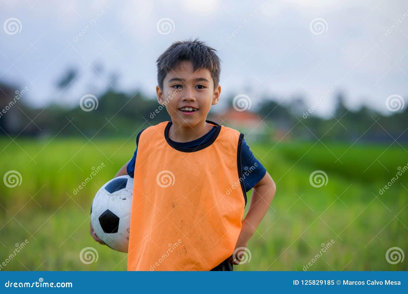 Livsstilstående av den hållande fotbollbollen för stilig och lycklig ung pojke som utomhus spelar fotboll på fältet för grönt grä