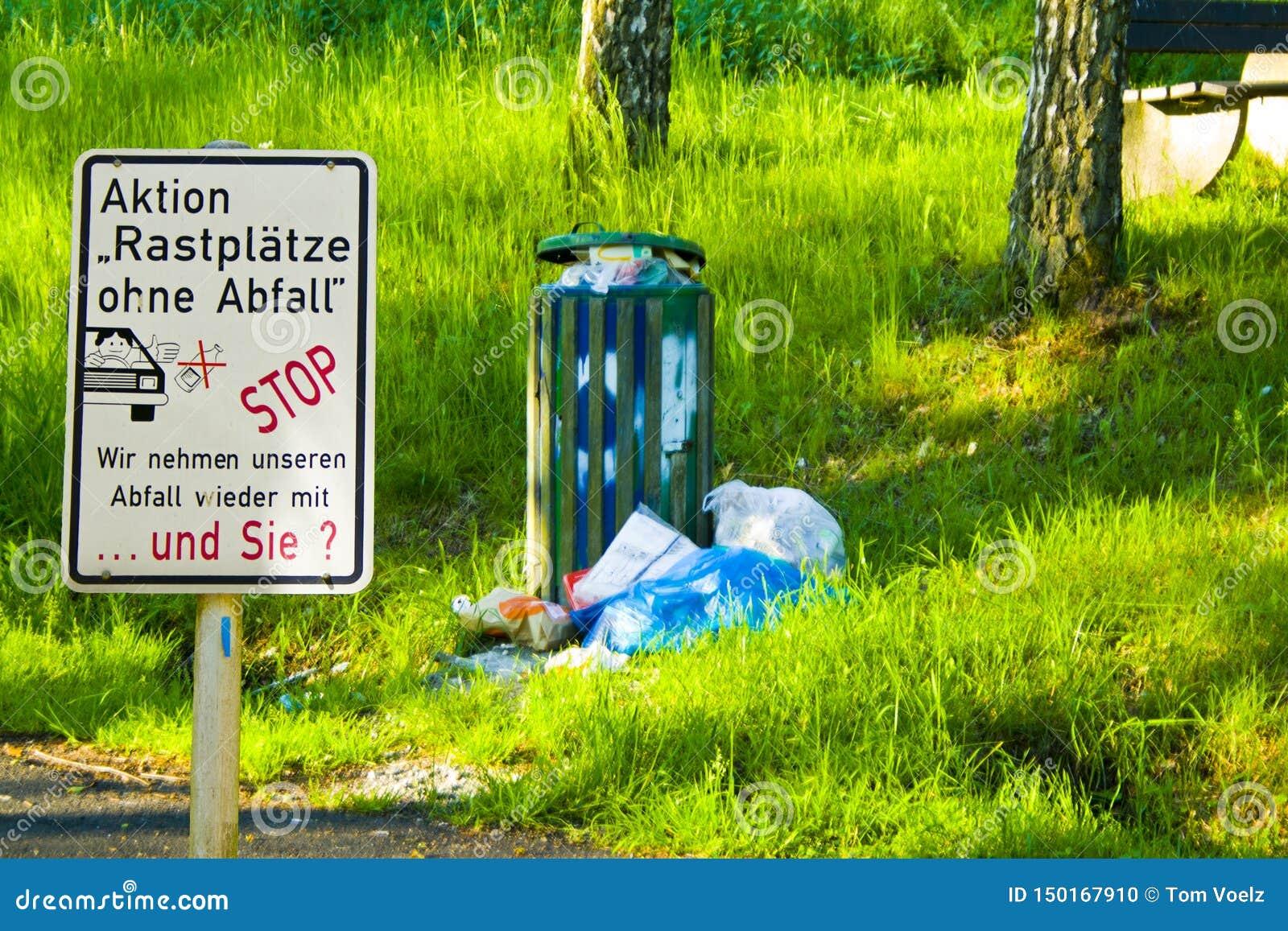 Lixo destituído em uma parada do resto em Hesse, Alemanha Com sinal