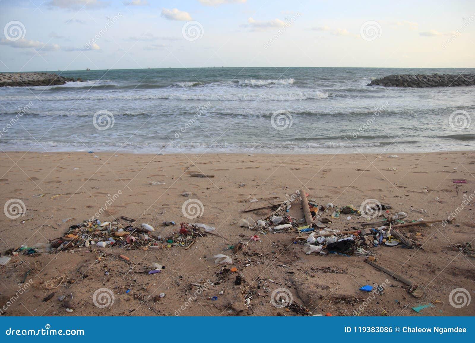 Lixo plástico, espuma, e desperdício sujo na praia no dia de verão
