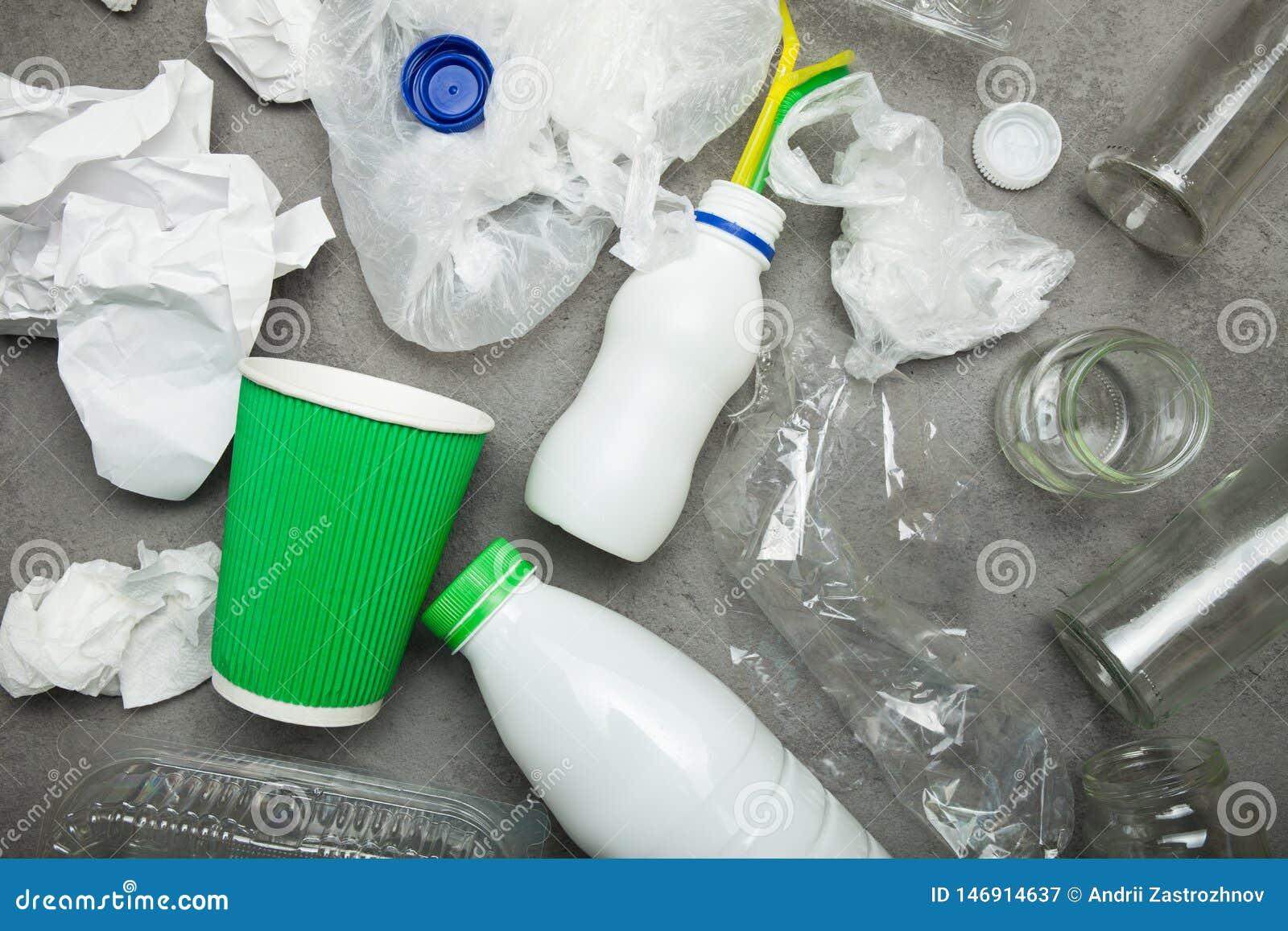 Lixo reciclável do fundo que consiste no vidro, no plástico, e no papel no concreto cinzento