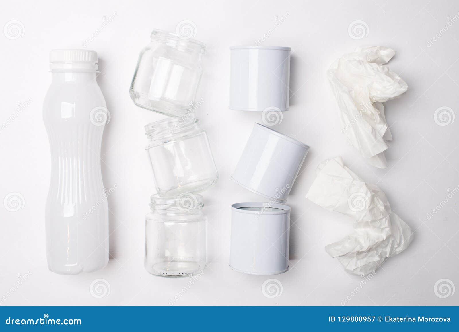 Lixo reciclável que consiste no vidro, no plástico, no metal e no papel no fundo branco Conceito branco da textura