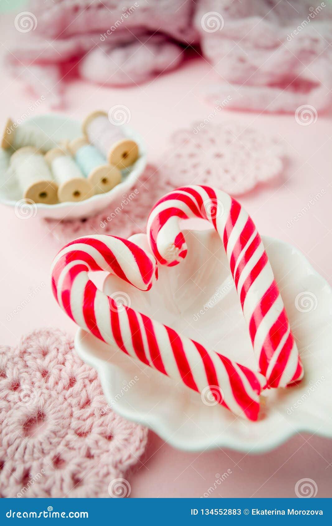 Lizaków cukierki jak serce na różowym pastelowym rocznika tle Pojęcie słodcy romantyczni sensy