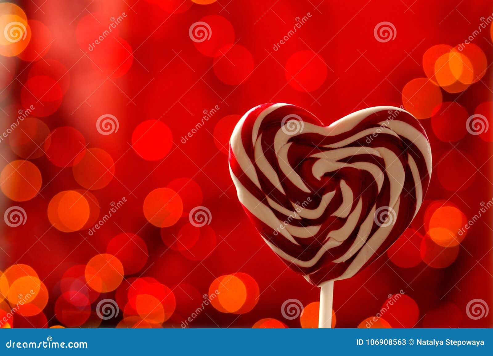 Lizak na sercu kształtował kij na czerwonym tle Bokeh