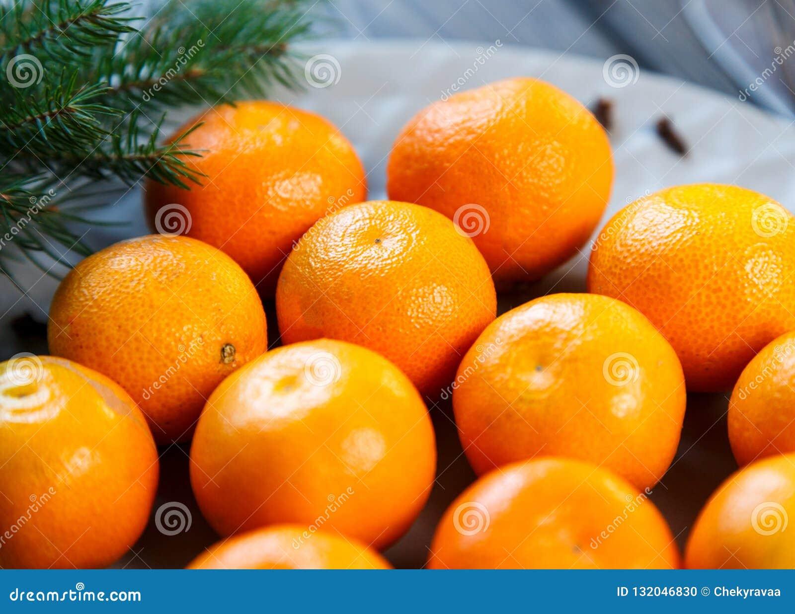 Ljus apelsin för tangerin som är mogen med gröna sidor på en grå platta med granfilialer på trätabellen jul som ställer in tabell
