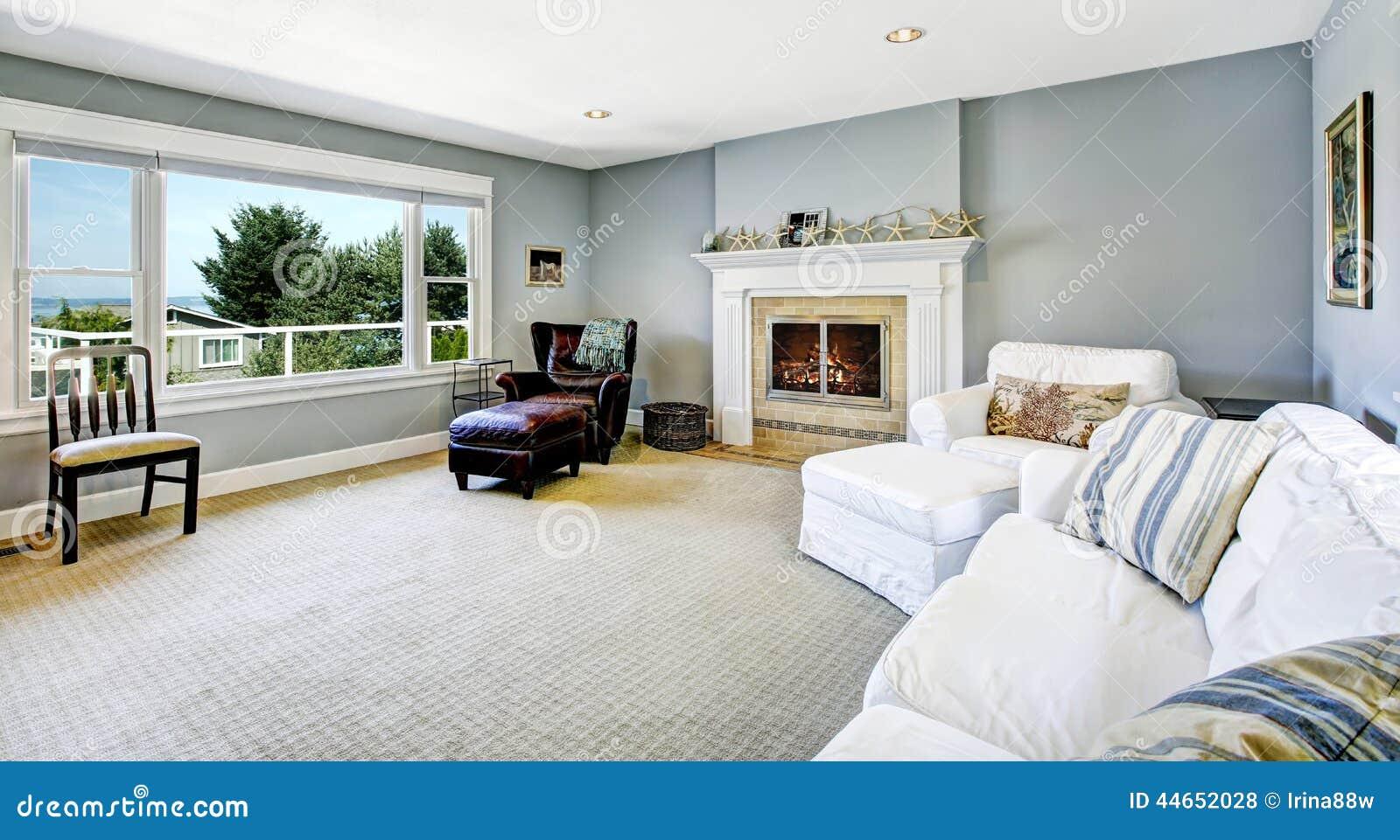 Ljus   blå vardagsrum med den vita soffan och spisen arkivfoto ...