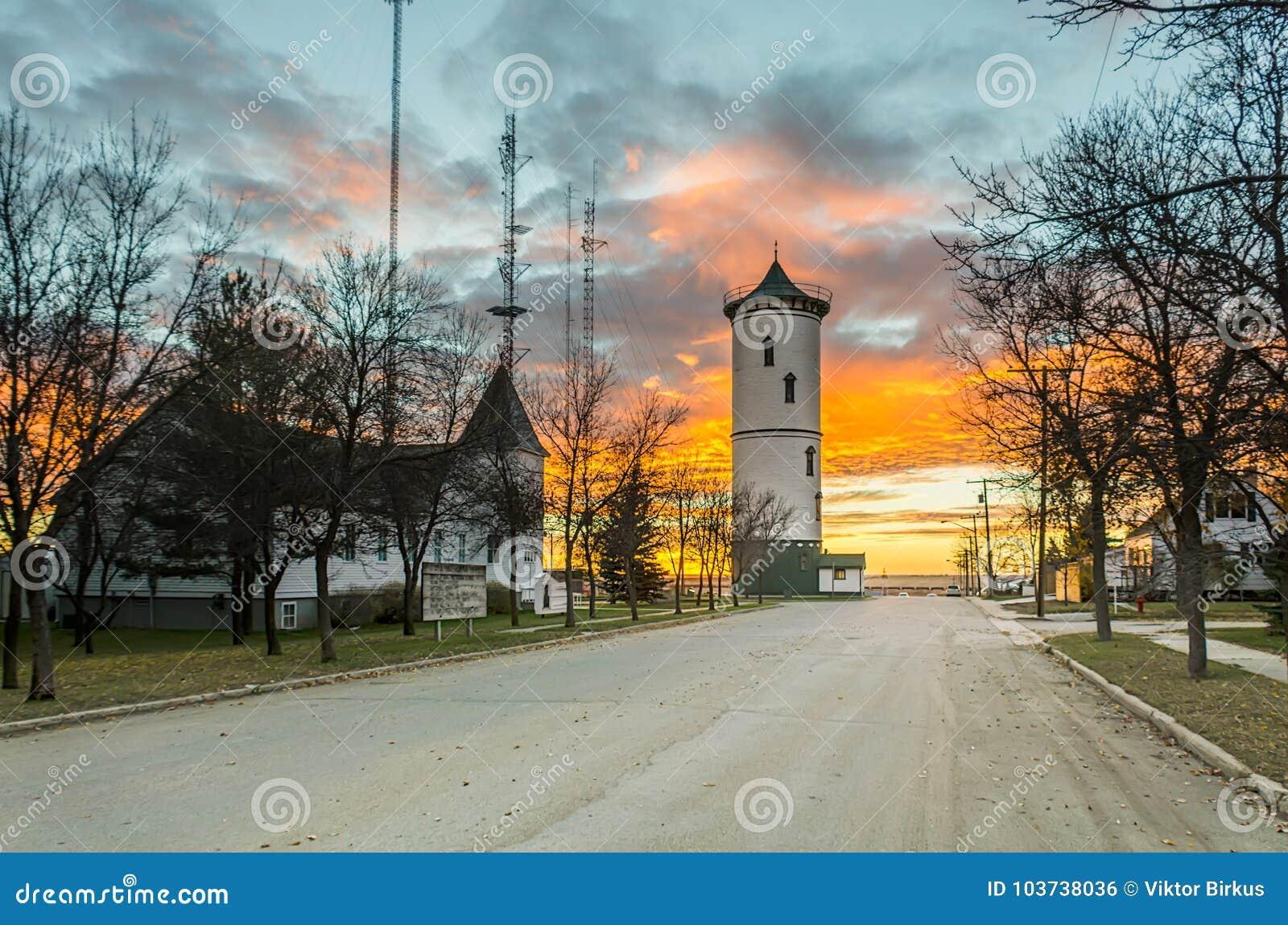 Ljus färgrik solnedgång i lilla staden med tornet och kyrka