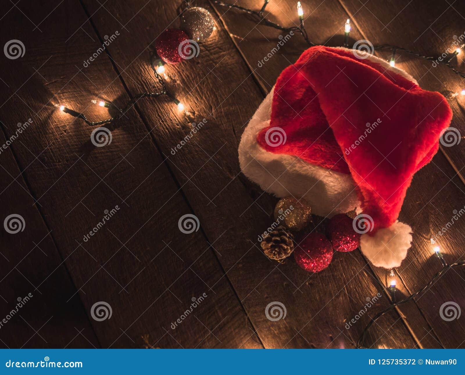 Ljus för jultomten hatt och julpå tappningträskrivbordet vita röda stjärnor för abstrakt för bakgrundsjul mörk för garnering mode
